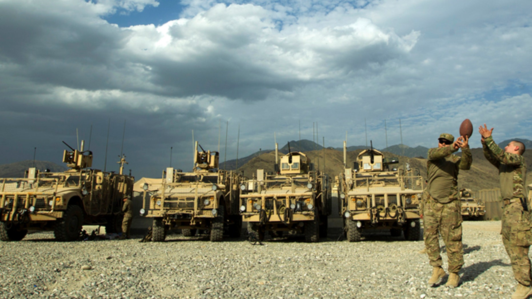 FILE: Soldiers of the 4th Brigade Combat Team, 4th Infantry Division play football in front of parked MRAP vehicles as they prepare to leave in a convoy inside FOB Joyce in Afghanistan's Kunar Province.