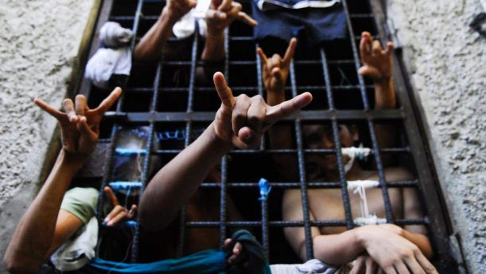 People arrested in El Salvador for being members of the MS-13 street gang flash their gang's hand signs from inside a jail cell.