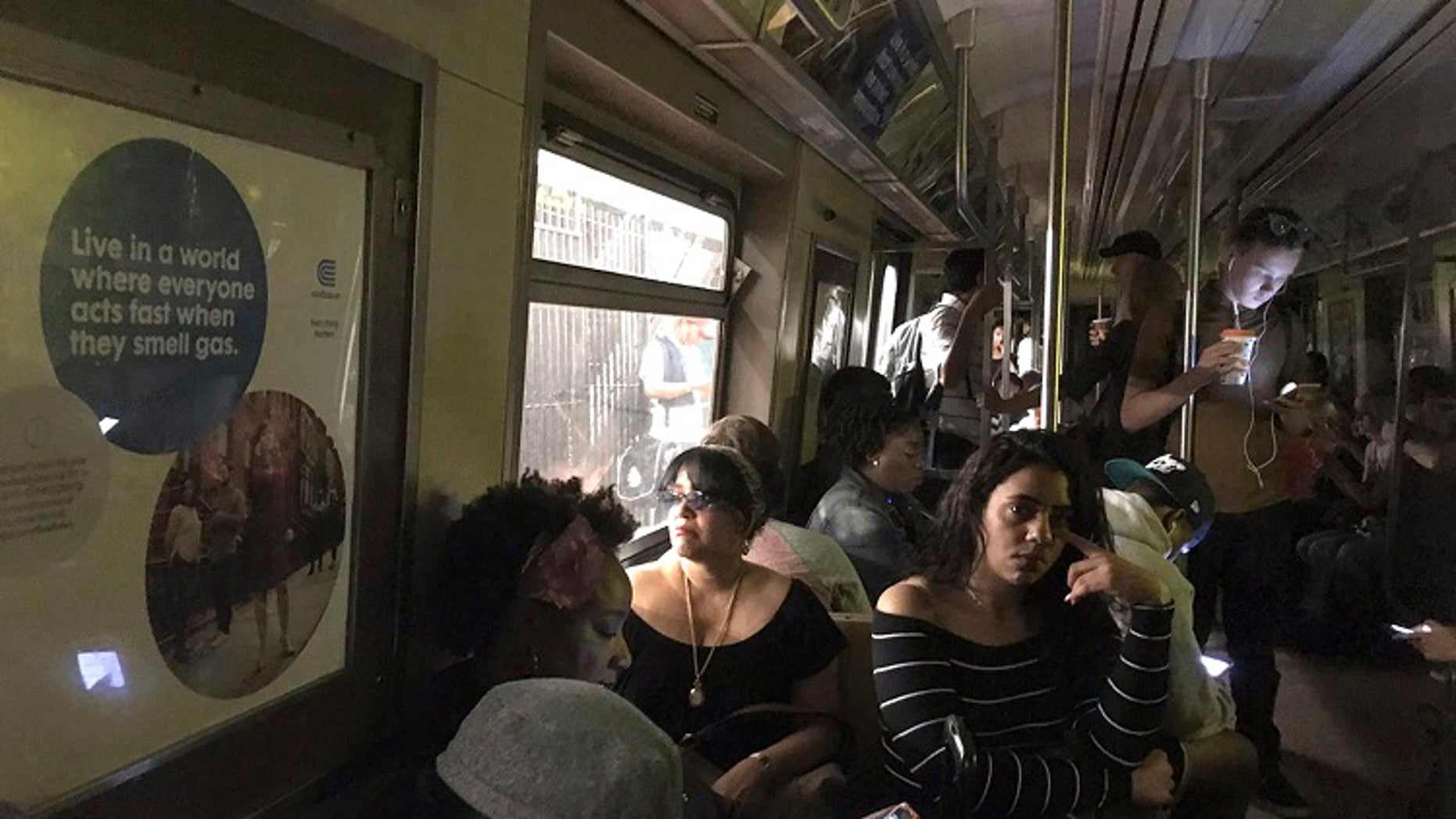 """New York City subway passengers wait on the """"A"""" train that derailed on Tuesday, June 27, 2017."""