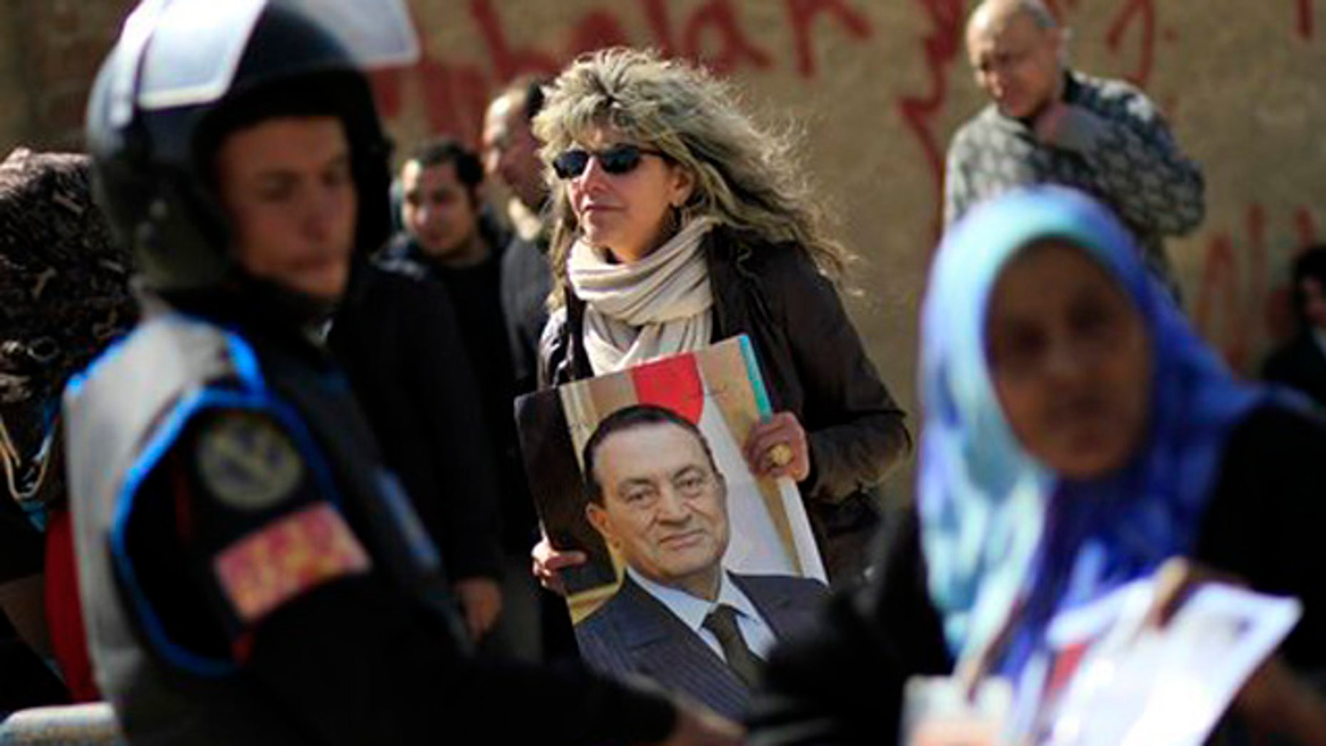 Feb. 22, 2012: An Egyptian woman holds a photo of the ousted Egyptian President Mubarak outside a courtroom in Cairo, Egypt.