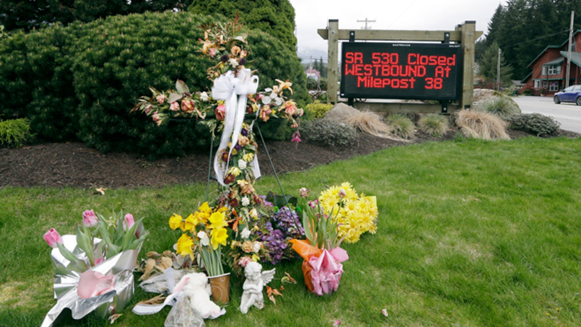 Apr. 15, 2014: A road sign advising the closure of Highway 530 stands near a small display of flowers and a cross in Darrington, Wash.