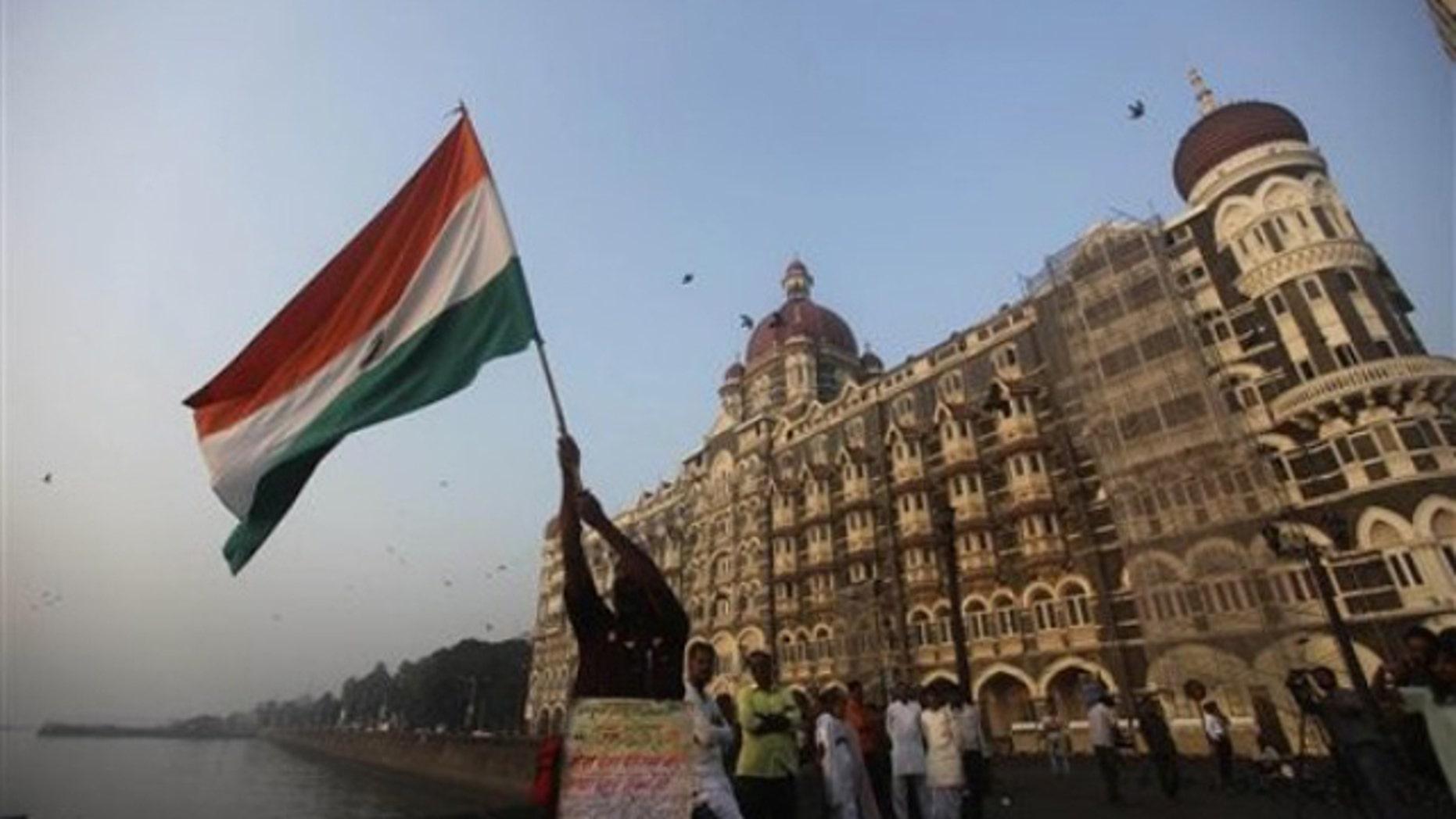 In this Nov. 26, 2009, file photo, a man waves an Indian flag outside the Taj Mahal hotel in Mumbai, India. (AP Photo)