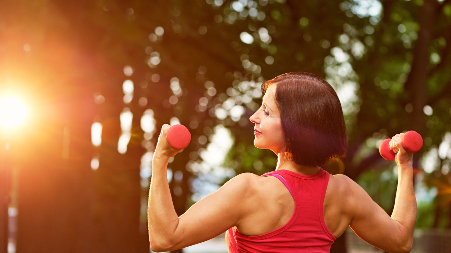 Aged woman working out with small dumbbells in the park in the morning.