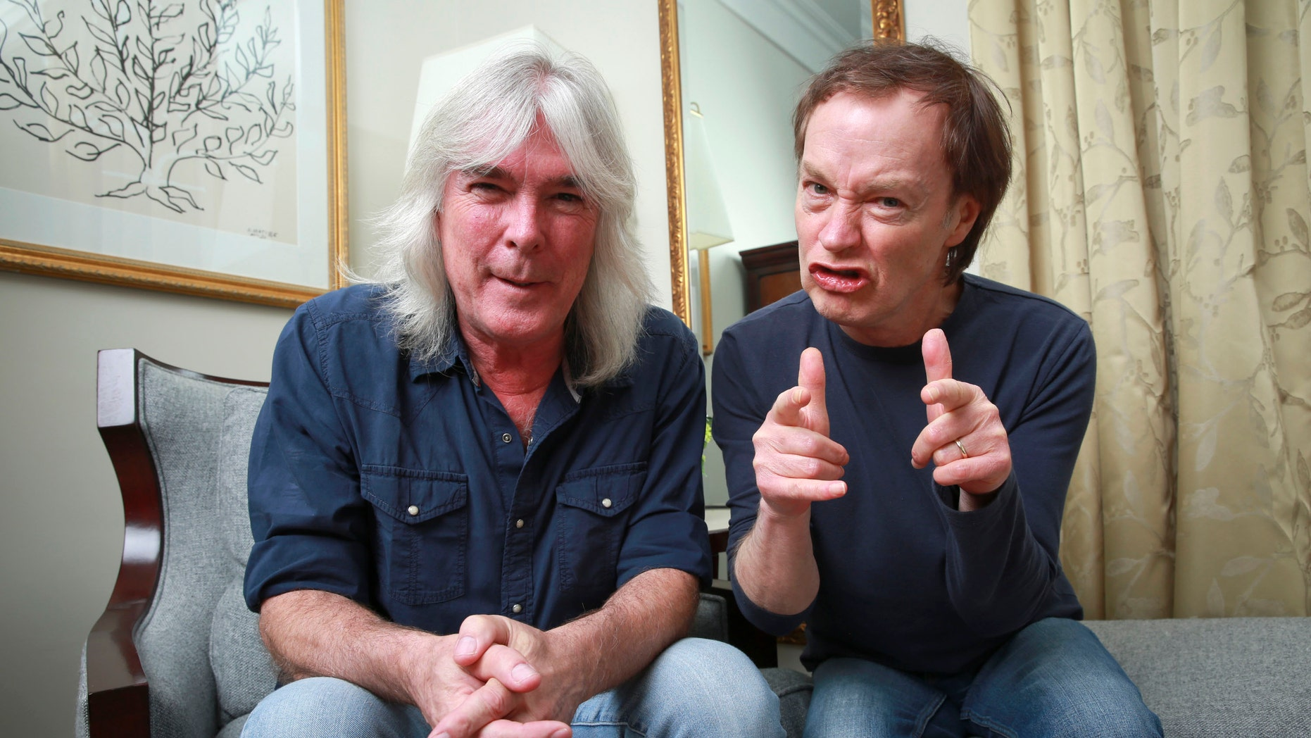"""In this Nov. 13, 2014 file photo, members of the rock band AC/DC, bassist Cliff Williams, left, and guitarist Angus Young pose for a portrait in promotion of their upcoming album, """"Rock or Bust"""" in New York."""