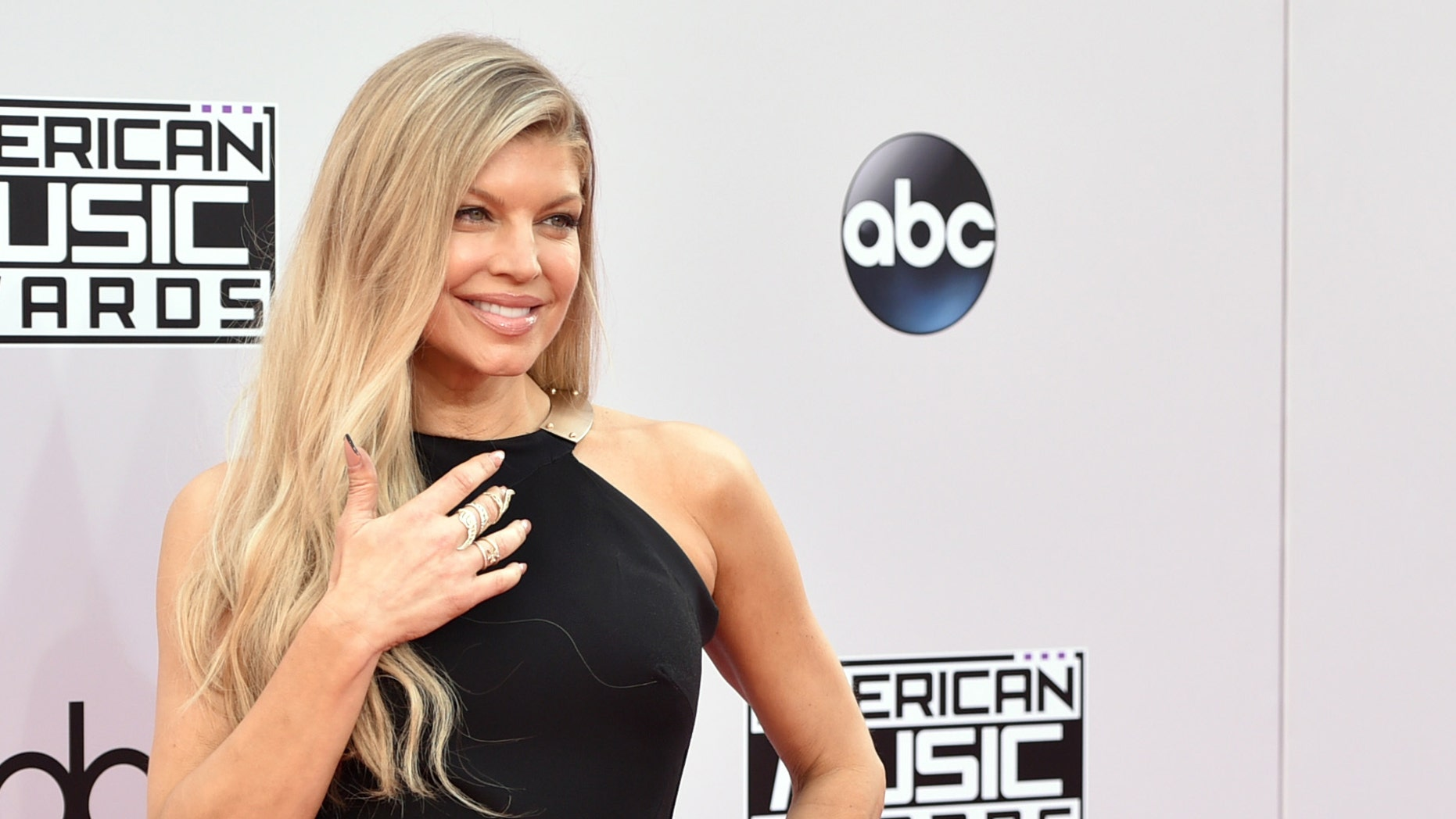 """FILE - In this Nov. 23, 2014, file photo, Fergie arrives at the 42nd annual American Music Awards at Nokia Theatre L.A. Live in Los Angeles. Fergie said the concept for her latest hit """"M.I.L.F. $"""" was in the works for several years, and she's hoping to inspire and empower mothers to find a balance between motherhood, career life and """"me time."""" The song and white-hot video, co-starring Kim Kardashian, Chrissy Teigen, Ciara and others, debuted Friday, July 1, 2016, and quickly became a trending topic on social media. (Photo by John Shearer/Invision/AP, File)"""