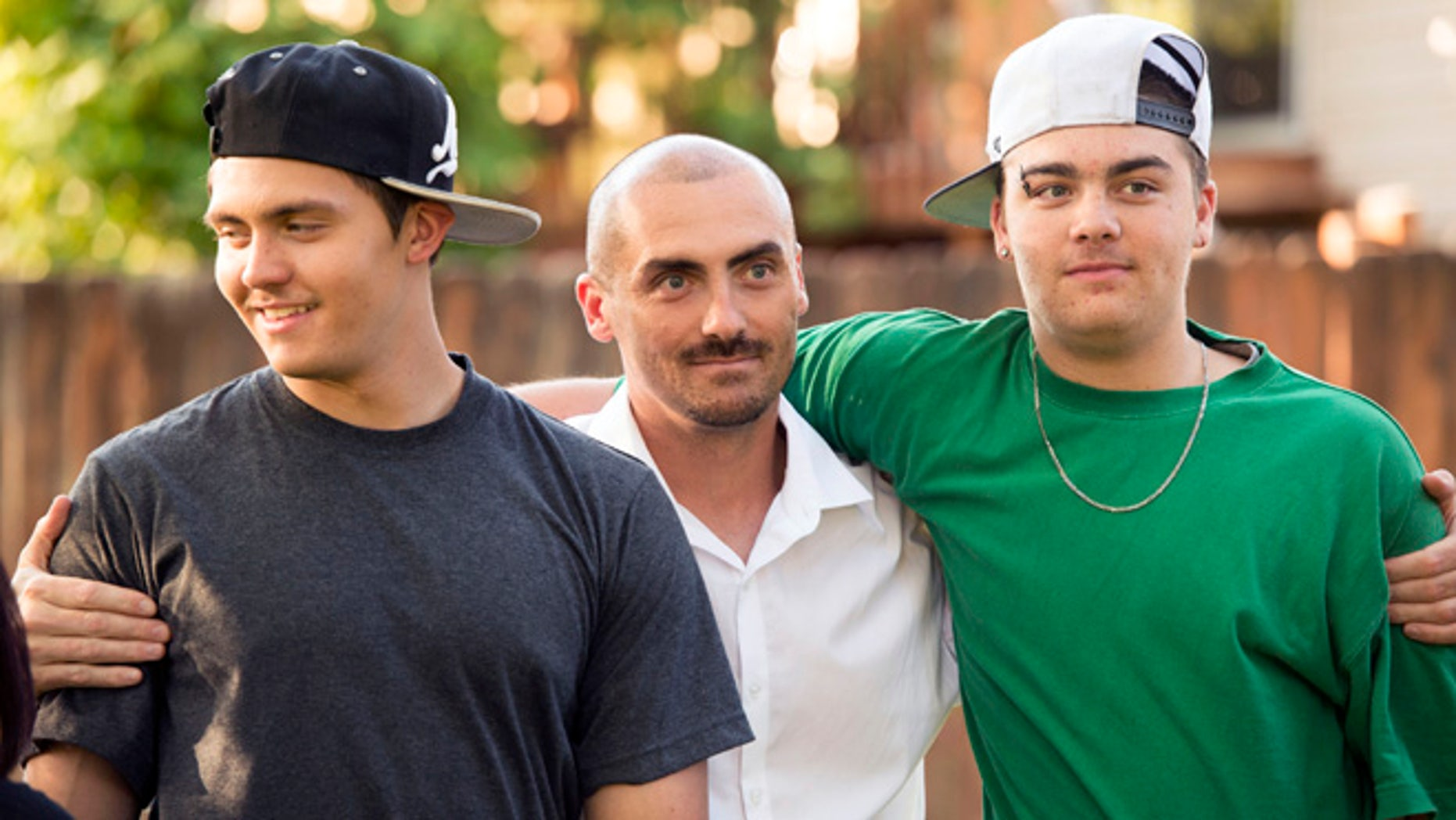 Weldon Angelos, center, holds his sons after being released from prison.