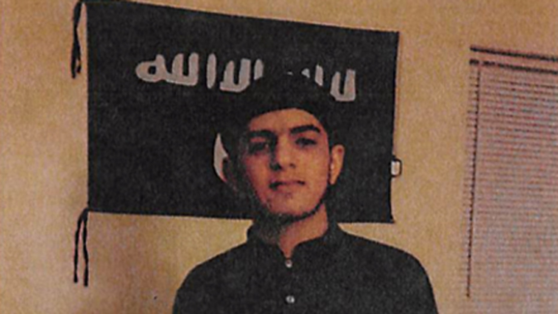 This image from June 2015 shows Akram Musleh, of Brownsburg, Ind., posing in front of an ISIS flag