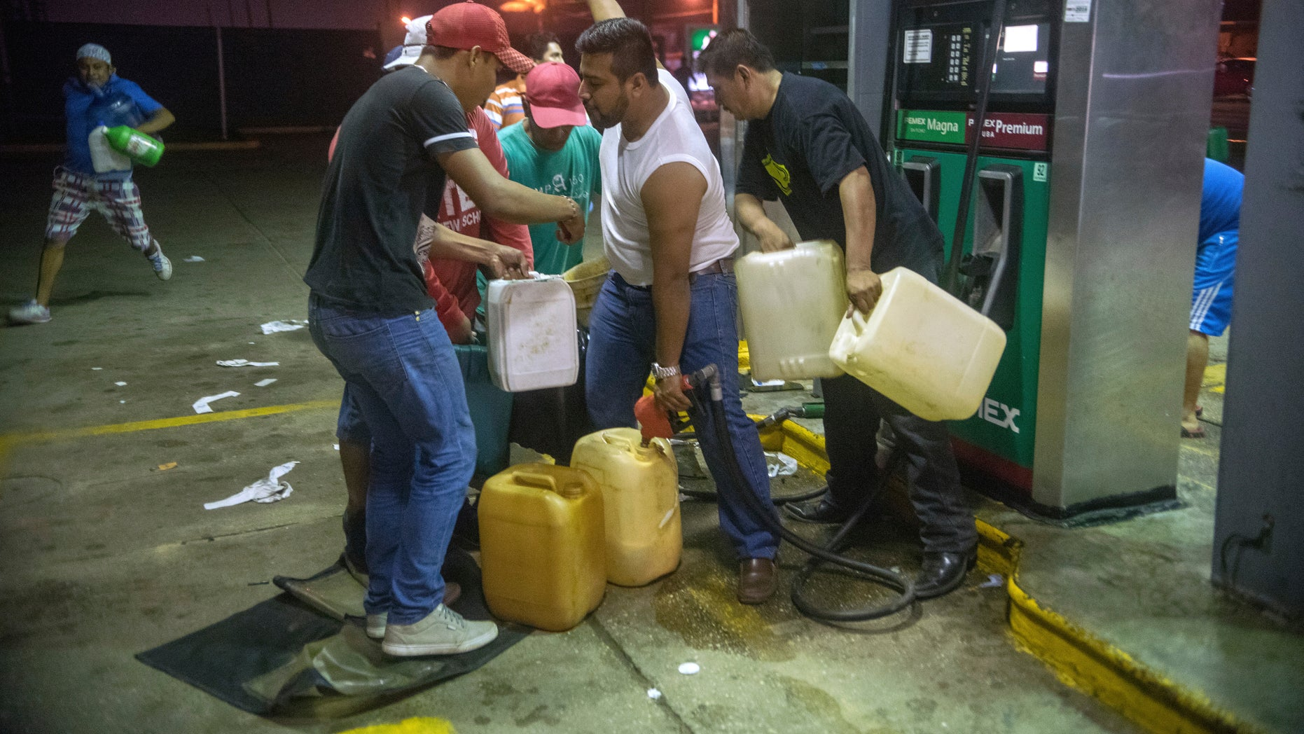 Residents pilfer gasoline and diesel from a gas station in Allende, Mexico, Jan. 3, 2017.
