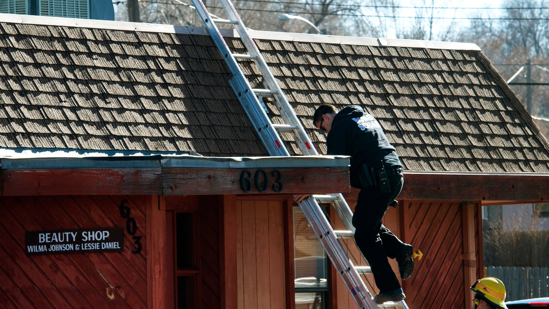 Jan. 6, 2015: A bomb squad member comes down from the roof as Colorado Springs police officers investigate the scene of an explosion Tuesday.