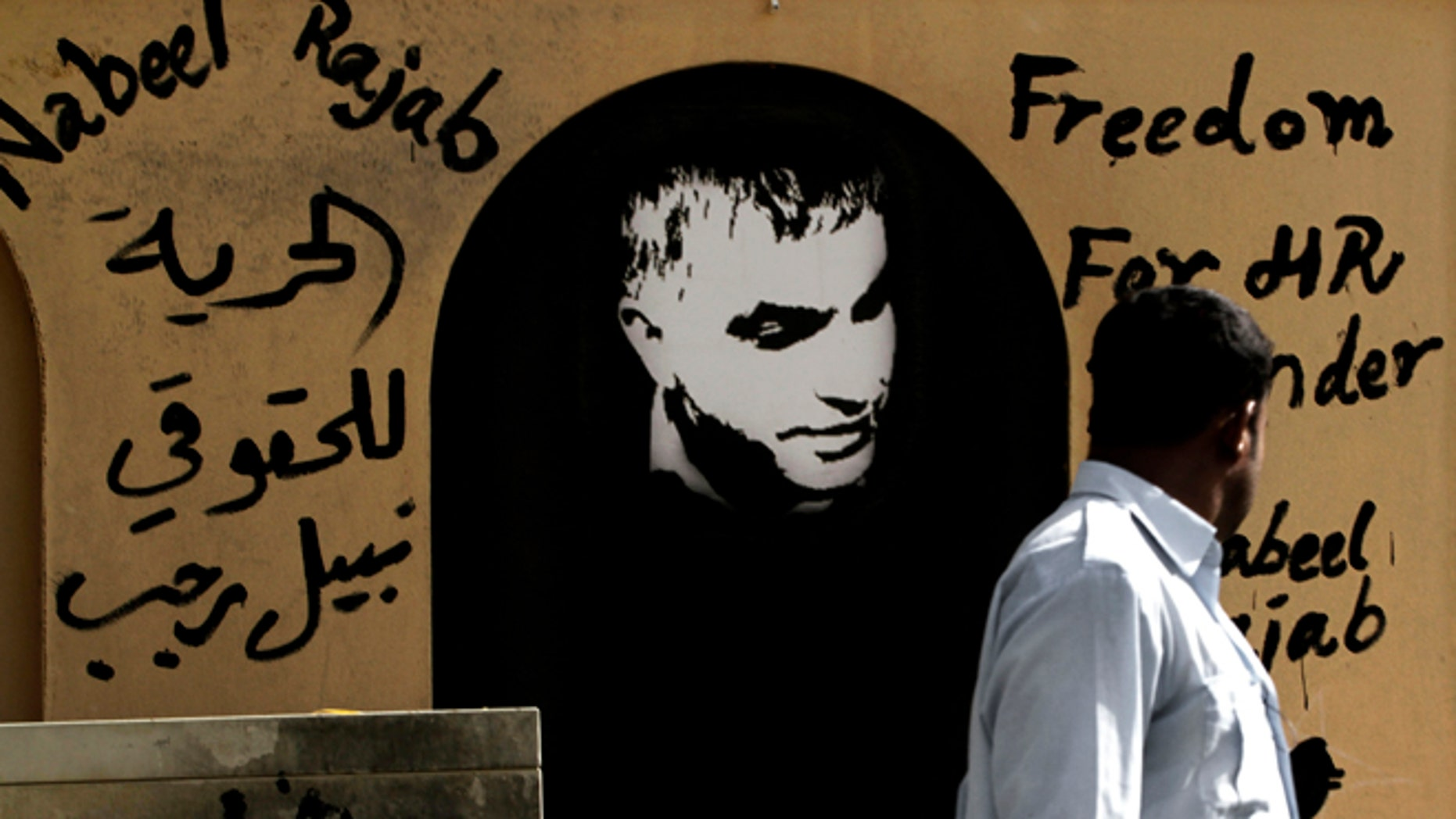 August 12, 2012: A man walks past a wall with human rights defender Nabeel Rajab, center, and Arabic, left, that reads, 'freedom to human rights defender Nabeel Rajab' on it in the northern village of Barbar, Bahrain.