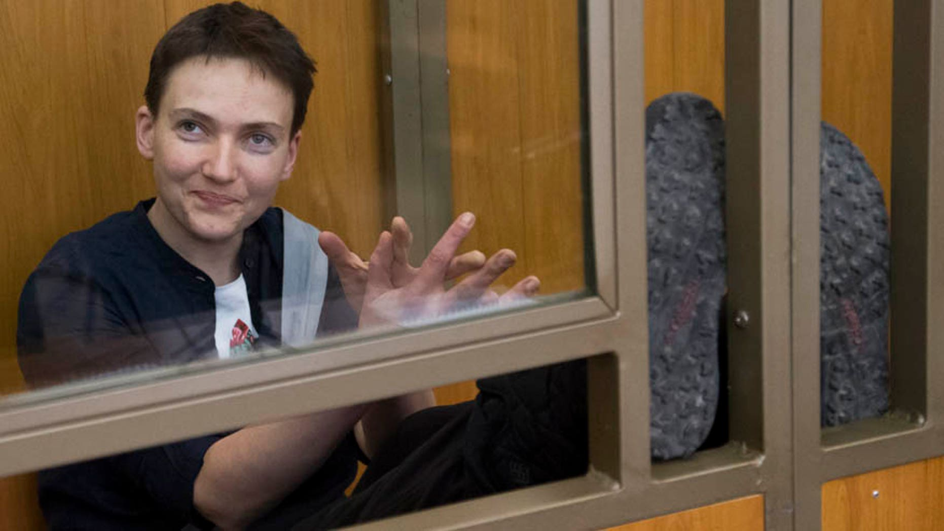 In this Tuesday, March 22, 2016 file photo Ukrainian pilot Nadezhda Savchenko looks out from a glass cage inside court, in the town of Donetsk, Rostov-on-Don region, Russia