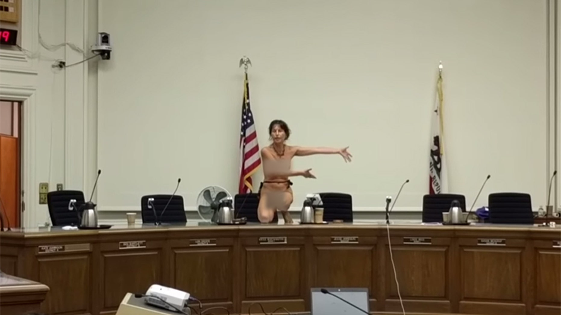 Activist Gypsy Taub climbs onto the dais after the Berkeley, Calif. City Council tabled a proposed ordinance that would allow women to go topless in public.