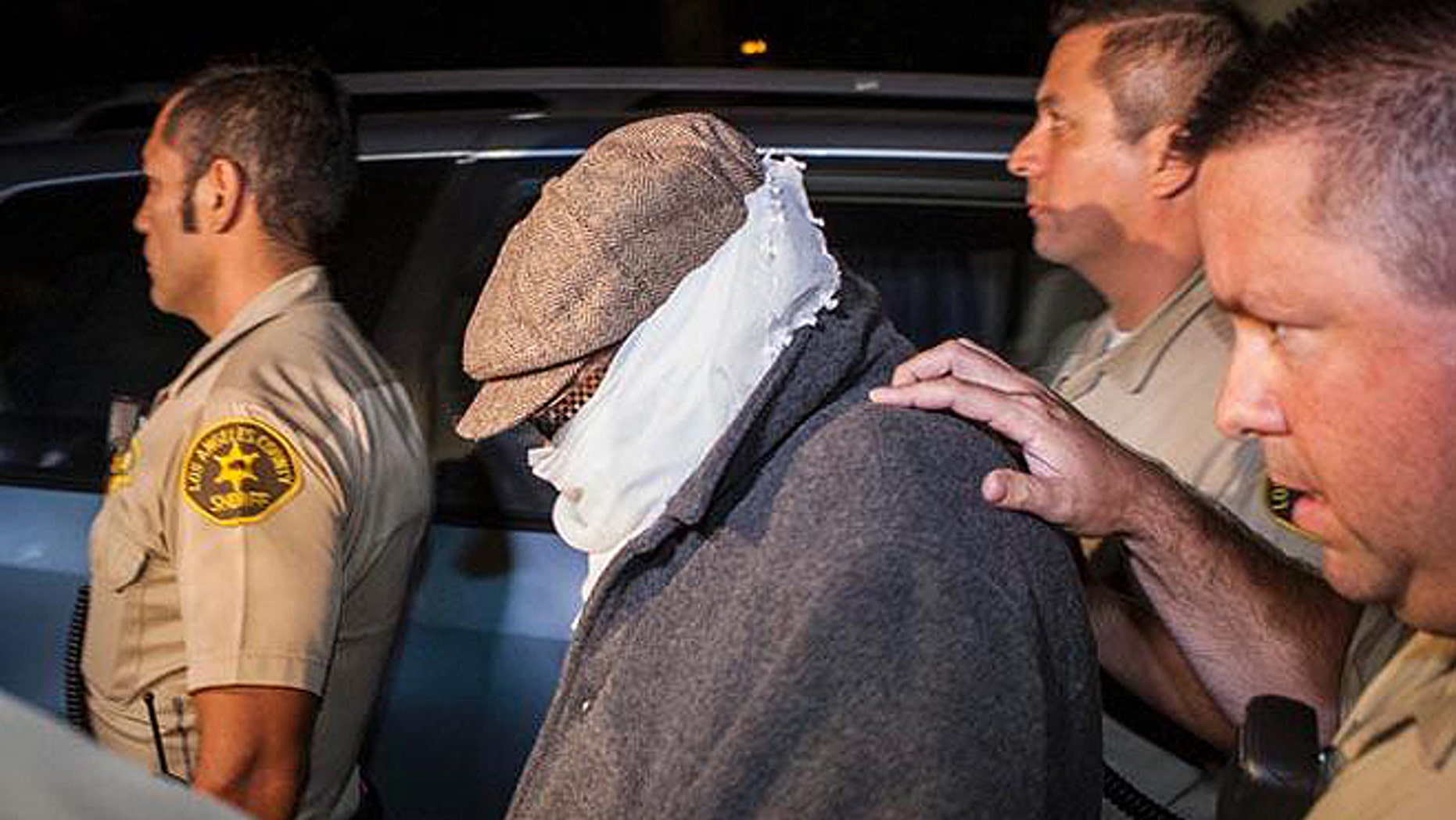 Nakoula, seen here in 2013 being escorted out of his home in Cerritos, Calif., lives under constant threat.