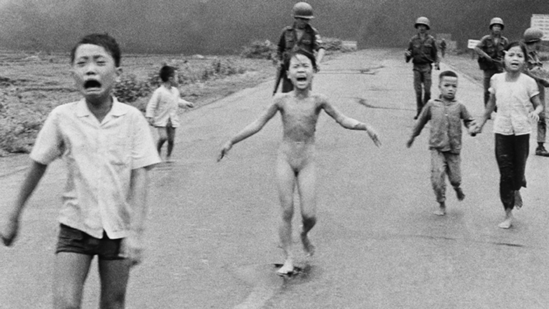In this June 8, 1972, file photo, 9-year-old Kim Phuc, center, runs with her brothers and cousins, followed by South Vietnamese forces, down Route 1 near Trang Bang after a South Vietnamese plane accidentally dropped its flaming napalm on its own troops and civilians. The terrified girl had ripped off her burning clothes while fleeing.