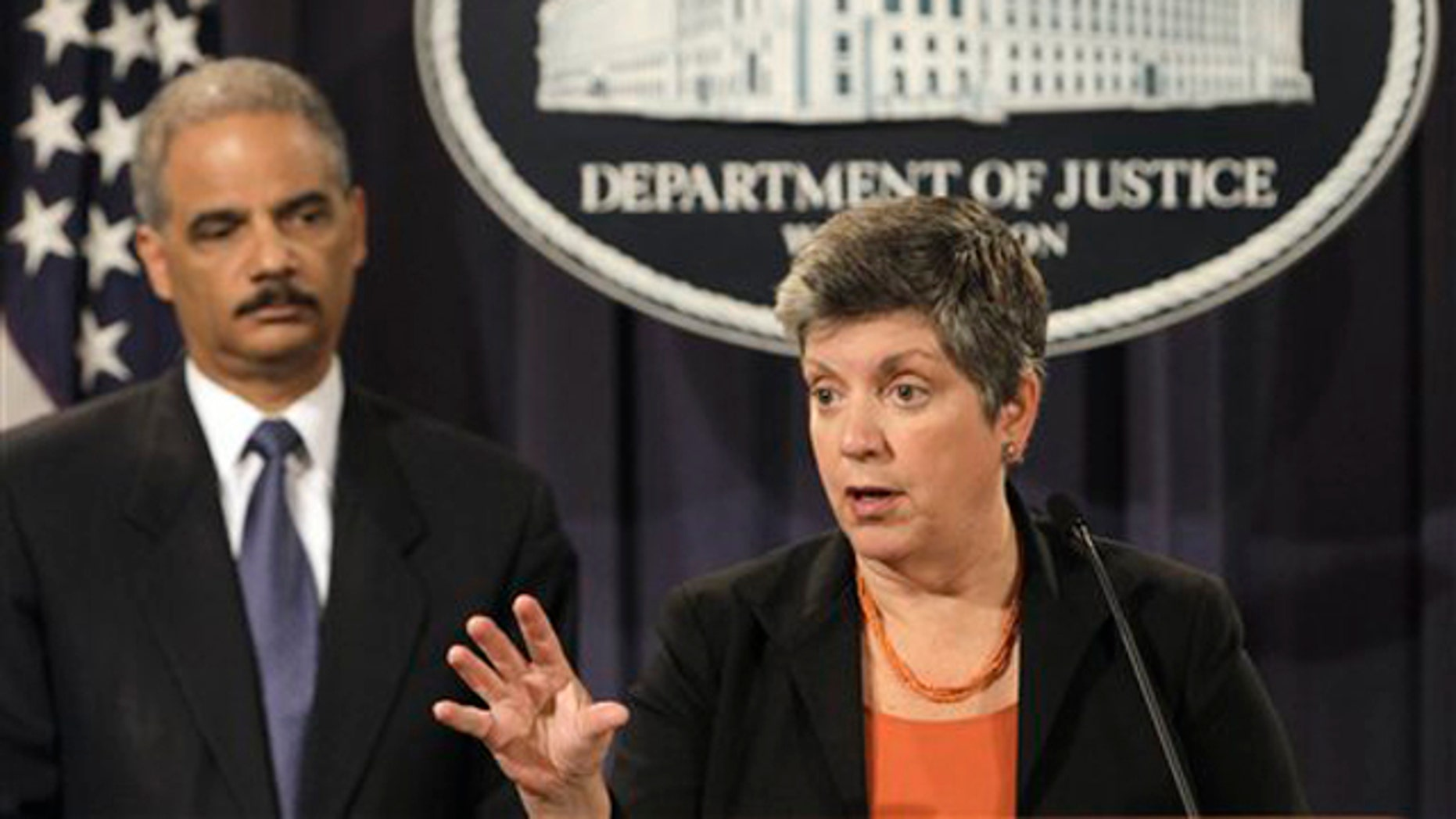 Attorney General Eric Holder, left, listens as Homeland Security Secretary Janet Napolitano speaks at the Justice Department in Washington Aug. 3.