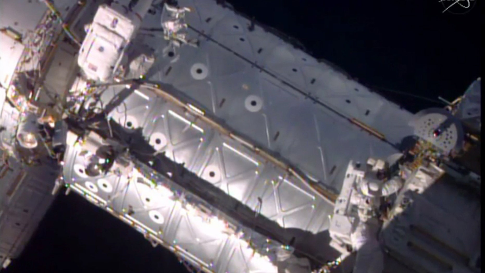 This image provided by NASA shows American astronauts Jeffrey Williams, left, and Kate Rubins taking a spacewalk to hook up a docking port outside the International Space Station on Friday, Aug. 19, 2016.  The docking port will be used by future commercial crew capsules.  SpaceX delivered this new gateway last month.   (NASA via AP)