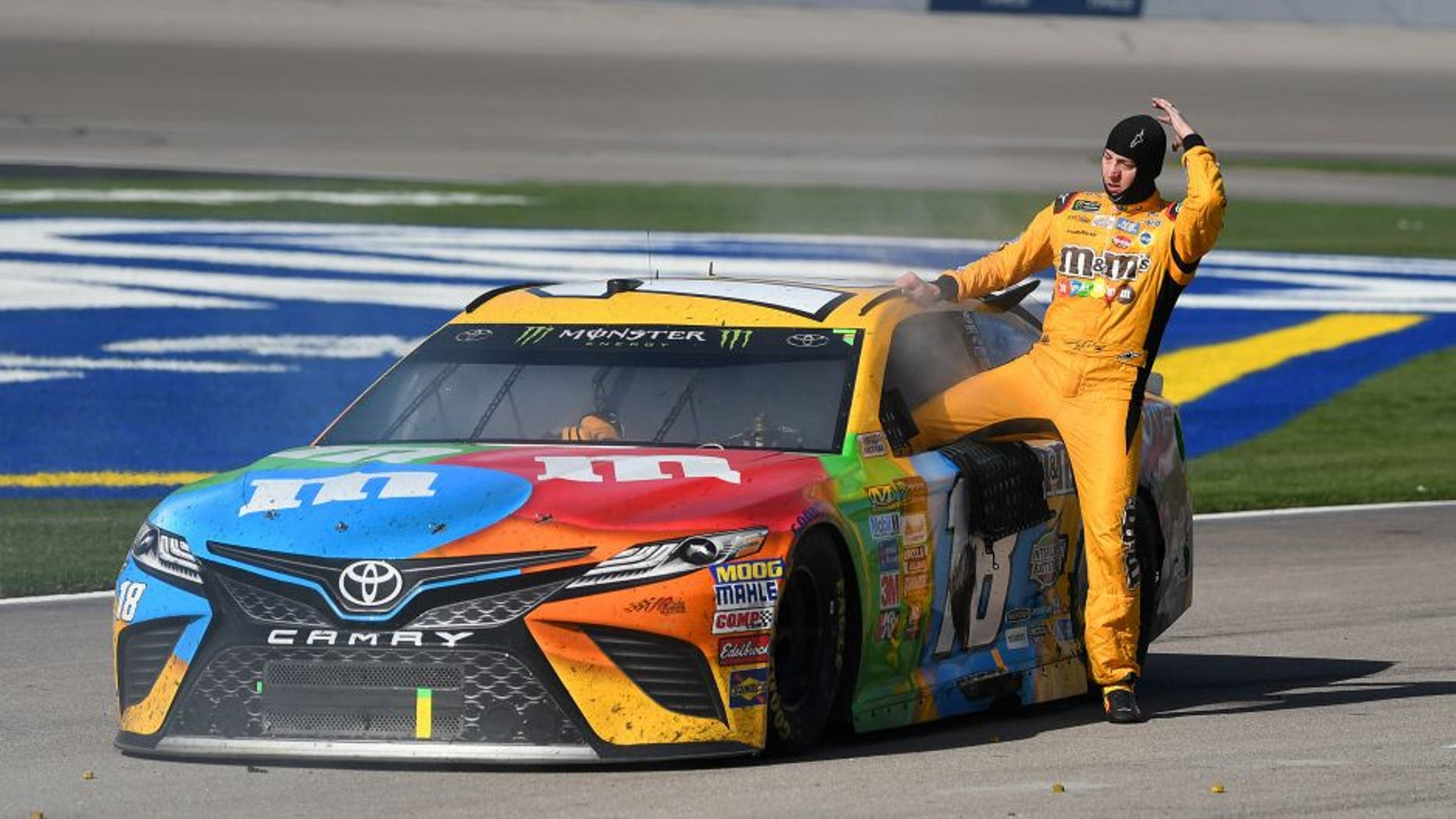Mar 12, 2017; Las Vegas, NV, USA; Kyle Busch (18) climbs out of the smoking cab of his car at the conclusion of the Kobalt 400 at Las Vegas Motor Speedway. Martin Truex Jr. won the race. Mandatory Credit: Stephen R. Sylvanie-USA TODAY Sports