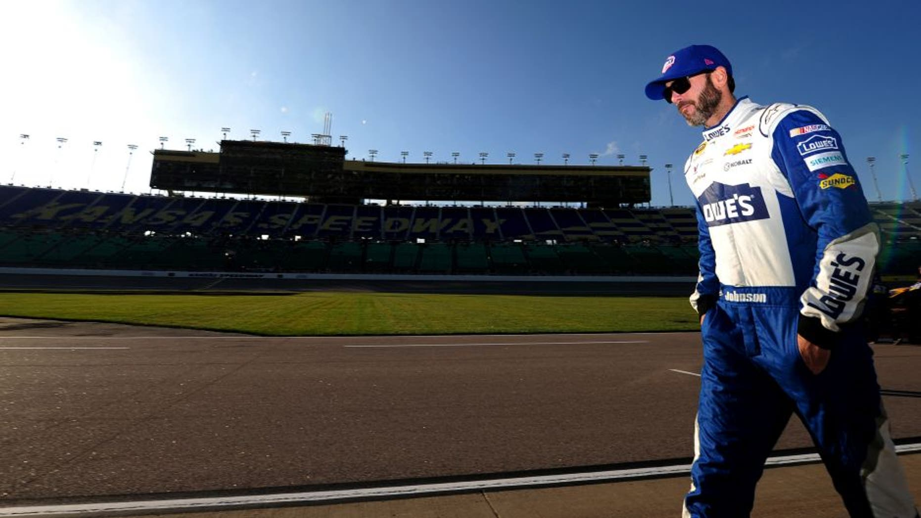 KANSAS CITY, KS - OCTOBER 14: Jimmie Johnson, driver of the #48 Lowe's Chevrolet, walks on the grid prior to qualifying for the NASCAR Sprint Cup Series Hollywood Casino 400 at Kansas Speedway on October 14, 2016 in Kansas City, Kansas. (Photo by Jeff Curry/Getty Images)