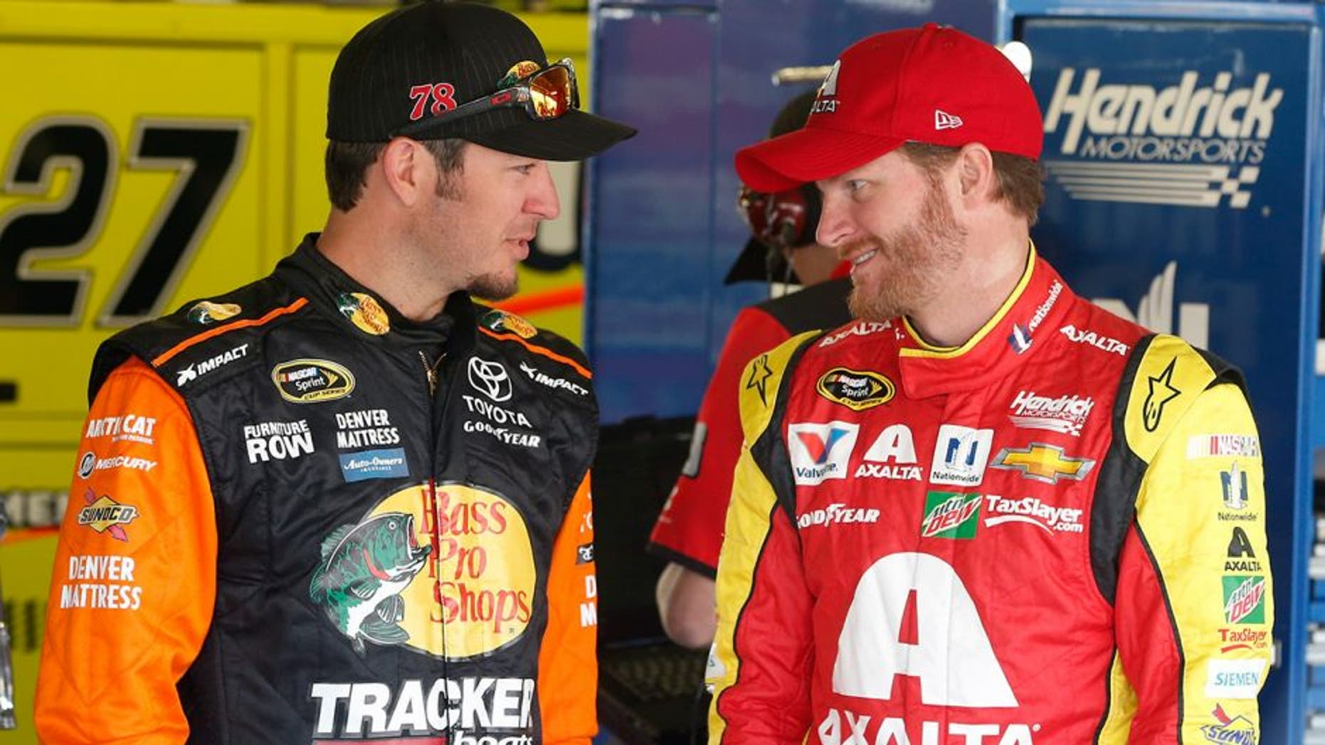 KANSAS CITY, KS - MAY 06: Martin Truex Jr., driver of the #78 Bass Pro Shops/TRACKER Boats Toyota Toyota, talks with Dale Earnhardt Jr., driver of the #88 Axalta Chevrolet, before practice for the NASCAR Sprint Cup Series Go Bowling 400 at Kansas Speedway on May 6, 2016 in Kansas City, Kansas. (Photo by Brian Lawdermilk/Getty Images)