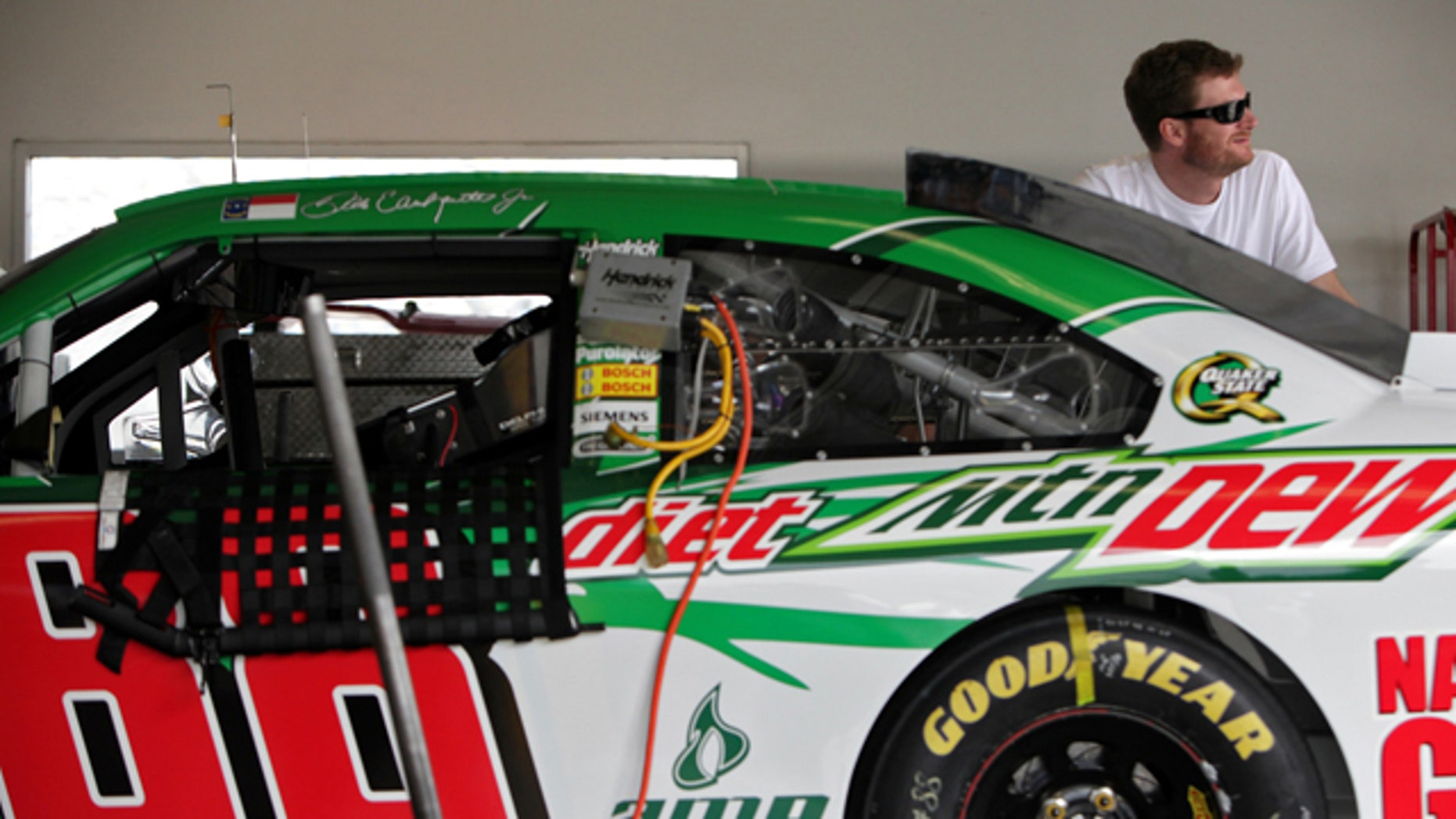 Dale Earnhardt Jr. peers out of the garage during NASCAR fuel-injection system testing at Daytona International Speedway in Daytona Beach, Fla., Tuesday, Nov. 15, 2011. (AP Photo/Daytona Beach News-Journal, Sean McNeil)