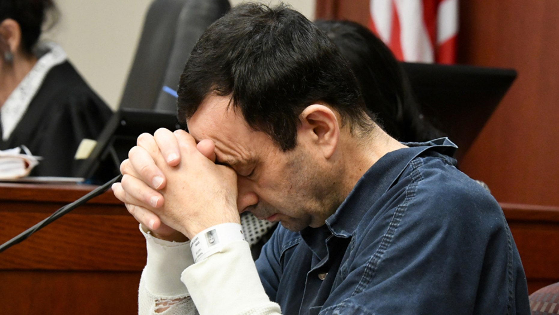 """A victim makes her """"impact statement"""" to Larry Nassar during a sentencing hearing as he puts his head down in front of Judge Rosemarie Aquilina in district court on Tuesday, Jan. 16, 2018, in Lansing, Mich. Nassar has pleaded guilty to molesting females with his hands at his Michigan State University office, his home and a Lansing-area gymnastics club,. (Dale G. Young/Detroit News via AP)"""