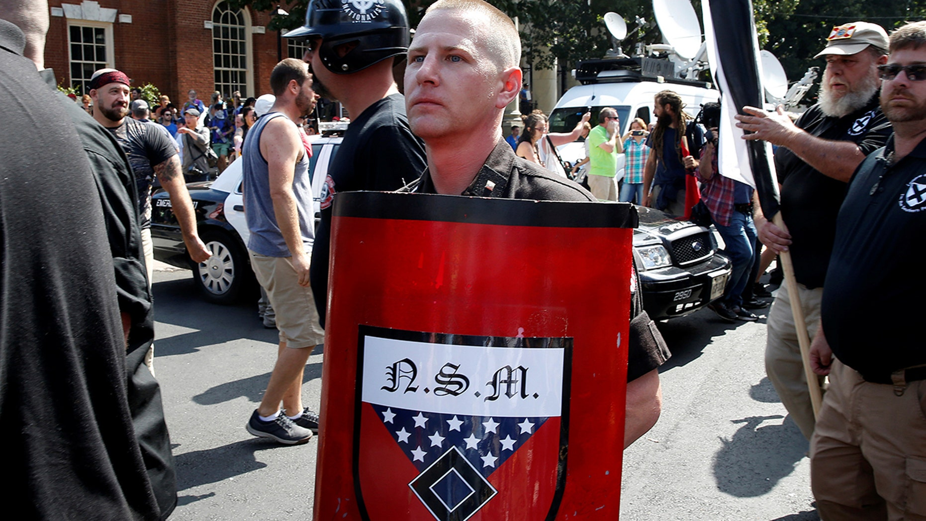 A white supremacist holds a shield with National Socialist Movement symbols on it as he arrives at a rally in Charlottesville, Va., Aug. 12, 2017.