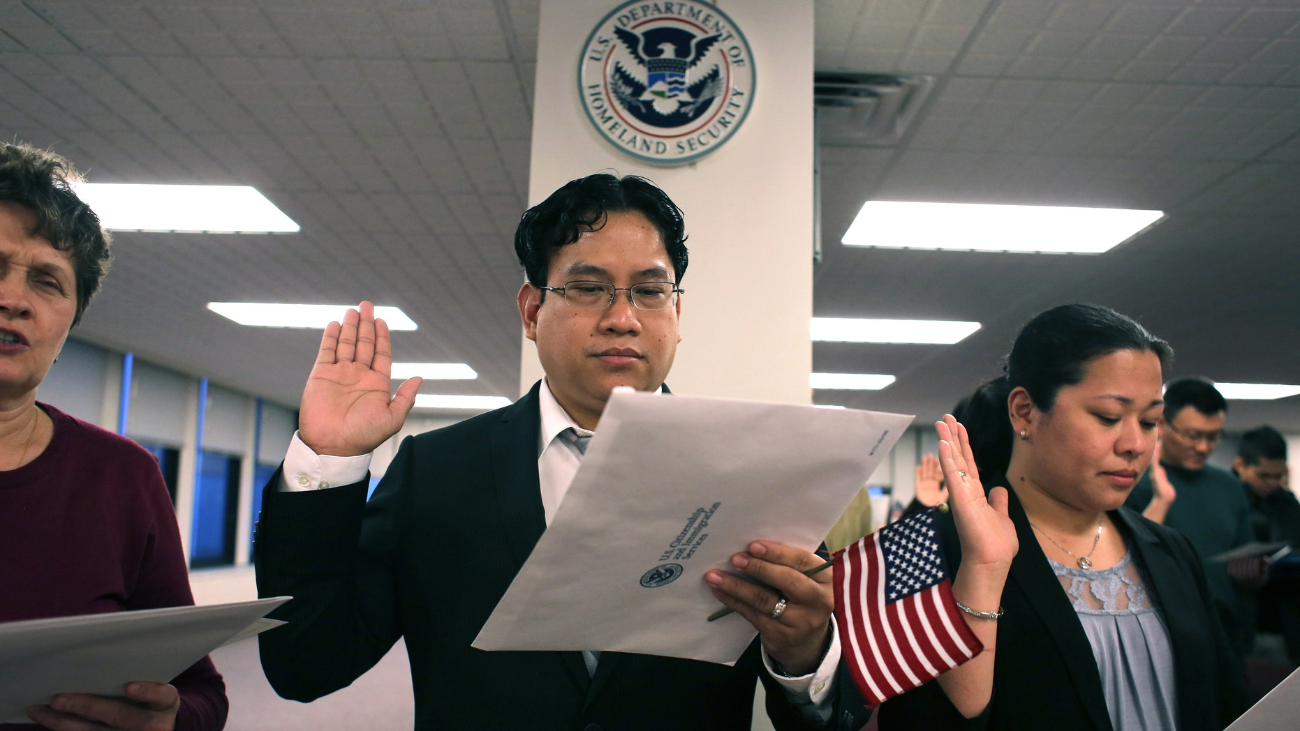 NEWARK, NJ - JANUARY 28:  Immigrants take the oath of allegiance to the United States during a ceremony at the district office of U.S. Citizenship and Immigration Services (USCIS) on January 28, 2013 in Newark, New Jersey. Some 38,000 immigrants became U.S. citizens at the Newark office alone in 2012.  (Photo by John Moore/Getty Images)
