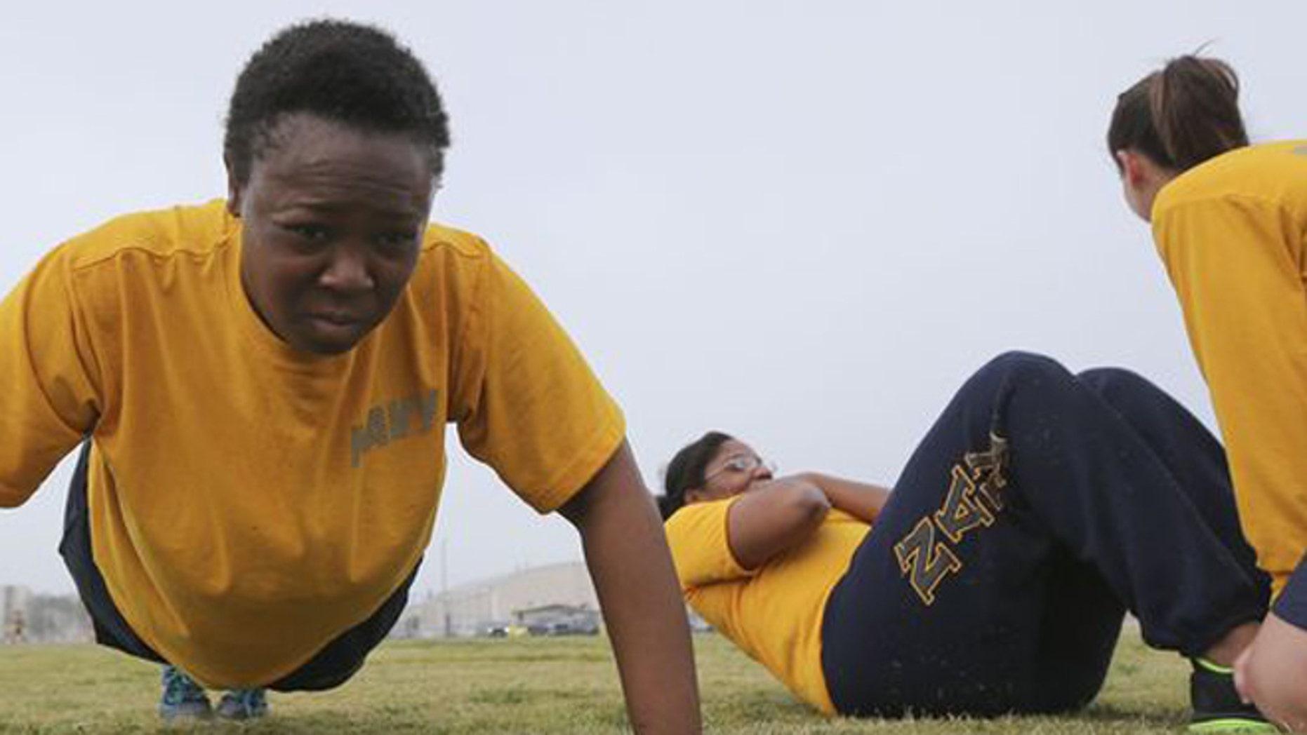 Petty Officer Lentoyi White does pushups while training with fellow Petty Officer Theresa White Monday, Feb. 29, 2016, in Coronado, Calif. (AP Photo/Lenny Ignelzi)
