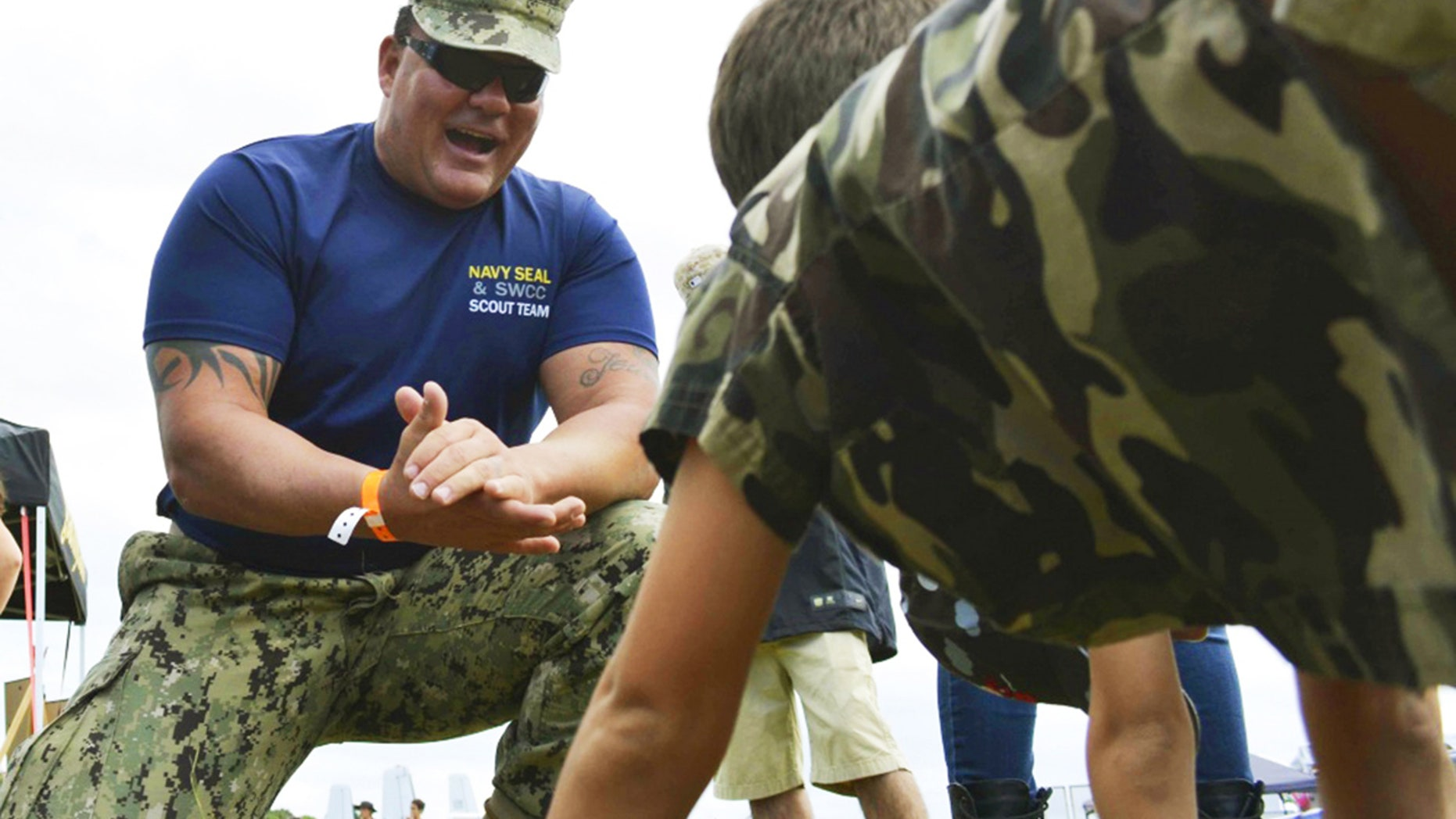 This Nov. 6. 2016 photo provided by the U.S. Navy shows Chief Petty Officer Joseph Schmidt III, assigned to the Navy SEAL and SWCC Scout Team, encouraging a young fan to do pushups at the 2016 Stuart Air Show in Stuart, Fla.