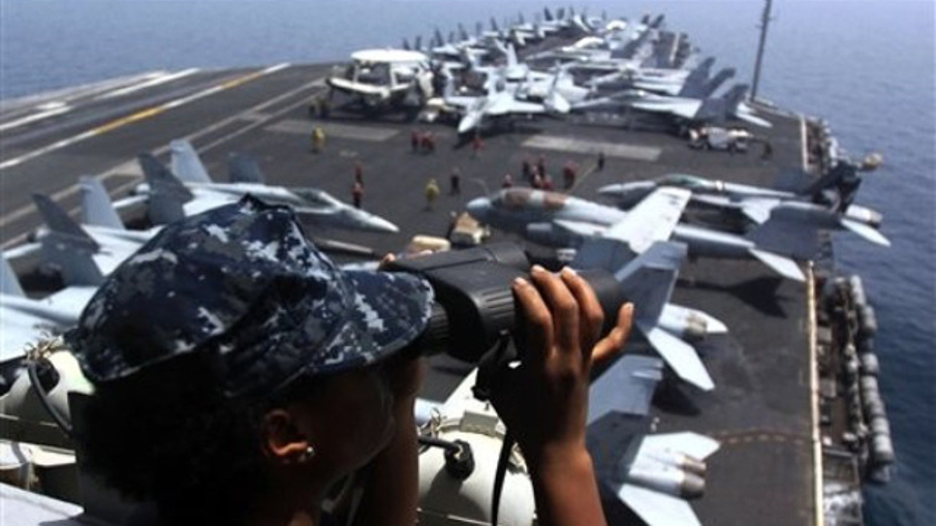 In this June 7 photo, a U.S. Navy sailor peers through binoculars from a lookout tower aboard the USS Dwight D. Eisenhower aircraft carrier in the Persian Gulf. (AP Photo)