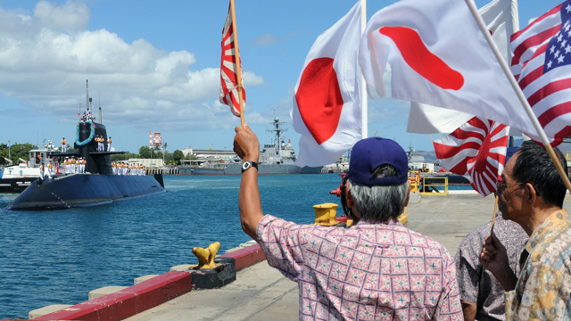 June 21, 2010: Onlookers wave as the Japanese Oyashio-class submarine J.S. Mochishio arrives at Joint Base Pearl Harbor-Hickam for Rim of the Pacific exercises. RIMPAC is a biennial, multi-national exercise designed to strengthen regional partnerships and improve multi-national interoperability.