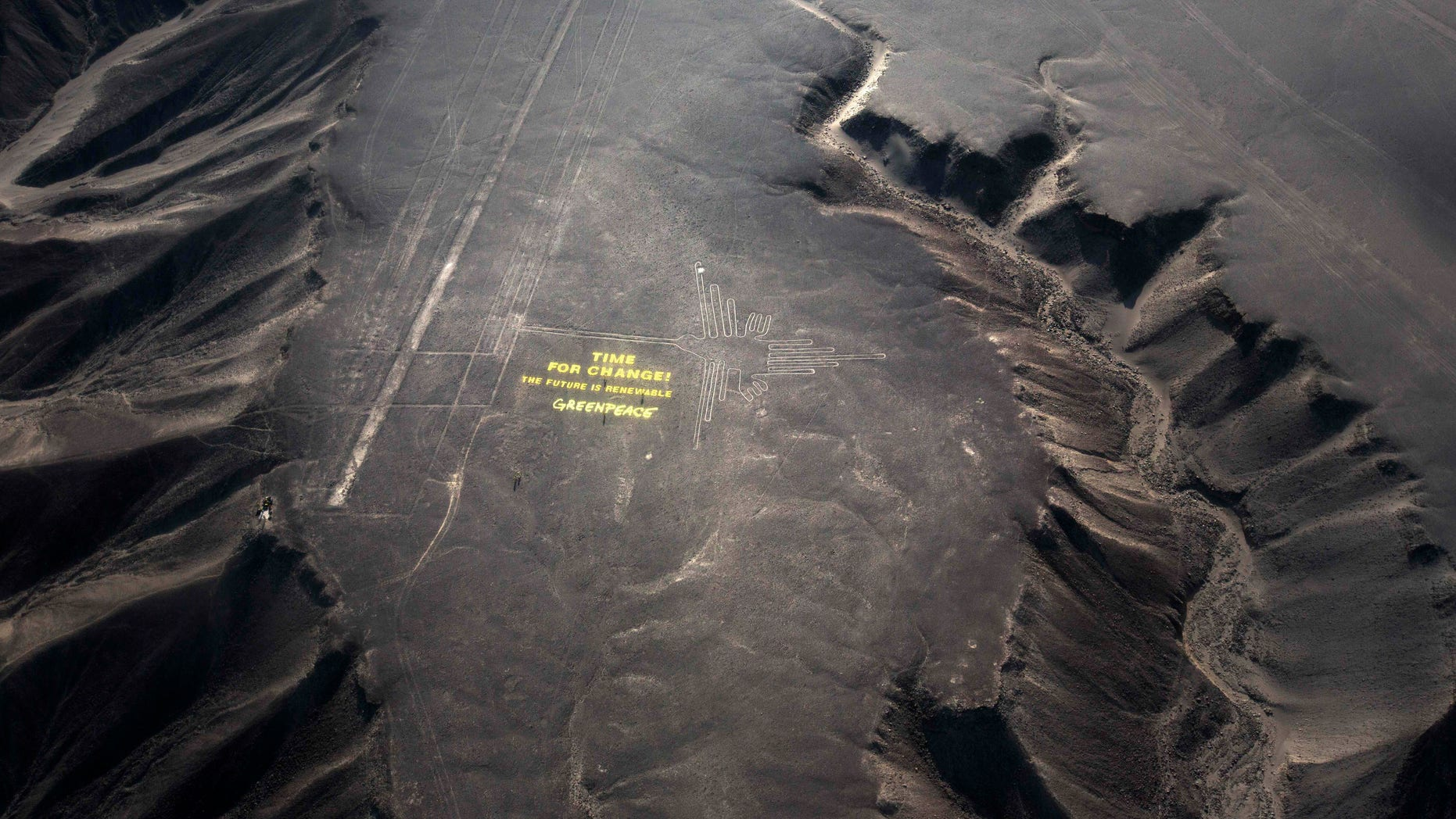 """Dec. 8, 2014: Greenpeace activists stand next to massive letters delivering the message """"Time for Change: The Future is Renewable,"""" next to the hummingbird geoglyph in Nazca in Peru"""