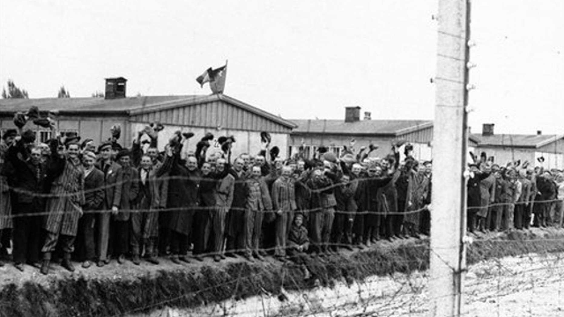 UNDATED: Prisoners at the electric fence of Dachau concentration camp cheer the Americans. German prosecutors say they are investigating a former Nazi concentration camp guard in the Berlin area on suspicion of murder after receiving a tip from the Simon Wiesenthal Center.