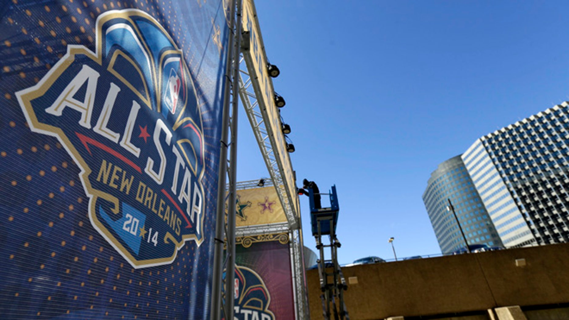 FILE - In this Feb. 13, 2014, file photo, a worker attaches a banner to a scaffolding in New Orleans in preparation of the NBA All-Star basketball game. (AP Photo/Gerald Herbert, File)