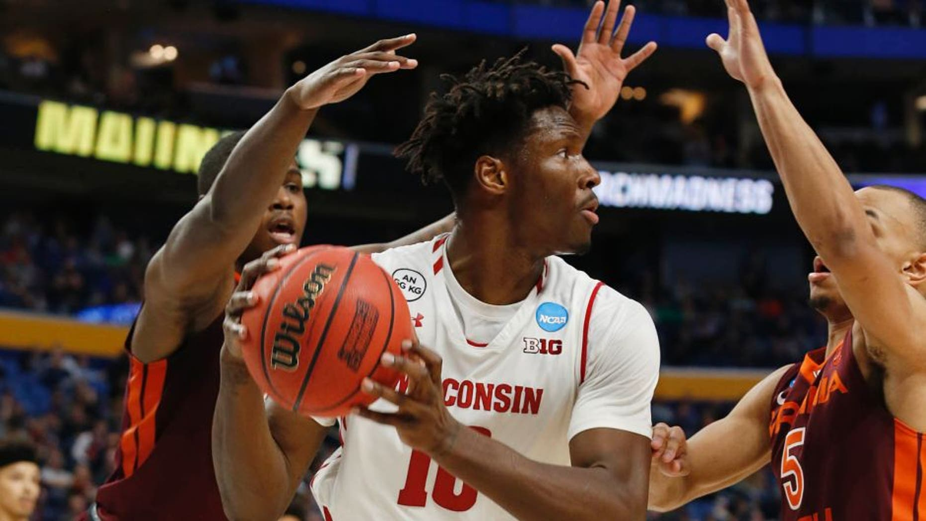 Mar 16, 2017; Buffalo, NY, USA; Wisconsin Badgers forward Nigel Hayes (10) is pressured by Virginia Tech Hokies guard Ty Outlaw (42) and guard Justin Robinson (5) in the second half during the first round of the NCAA Tournament at KeyBank Center. Mandatory Credit: Timothy T. Ludwig-USA TODAY Sports