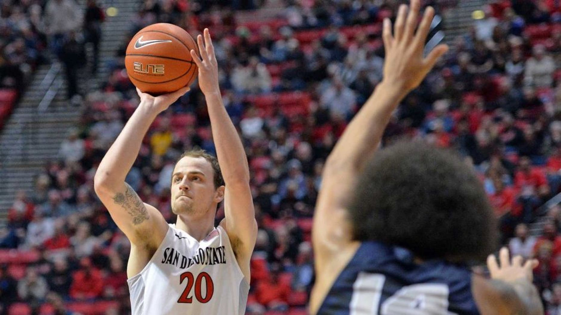 Jan 14, 2017; San Diego, CA, USA; San Diego State Aztecs forward Matt Shrigley (20) attempts a shot while defended by Utah State Aggies forward Jalen Moore (14) during the first half at Viejas Arena at Aztec Bowl. Mandatory Credit: Jake Roth-USA TODAY Sports