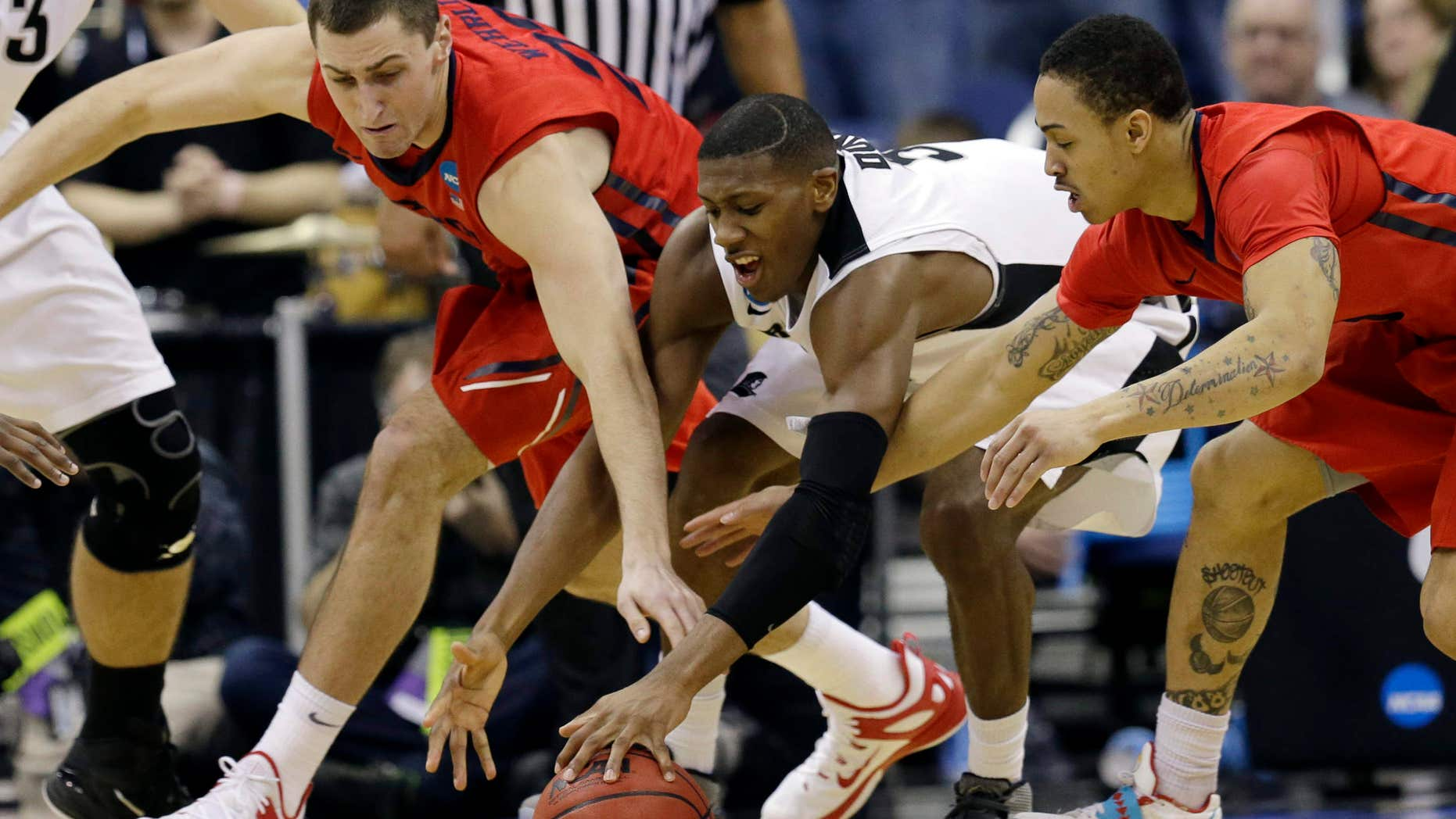 March 21, 2015: Dayton's Bobby Wehrli, left, and Kyle Davis, right, go for a loose ball against Providence's Kris Dunn in the second half of an NCAA tournament college basketball game in the Round of 64 in Columbus, Ohio.