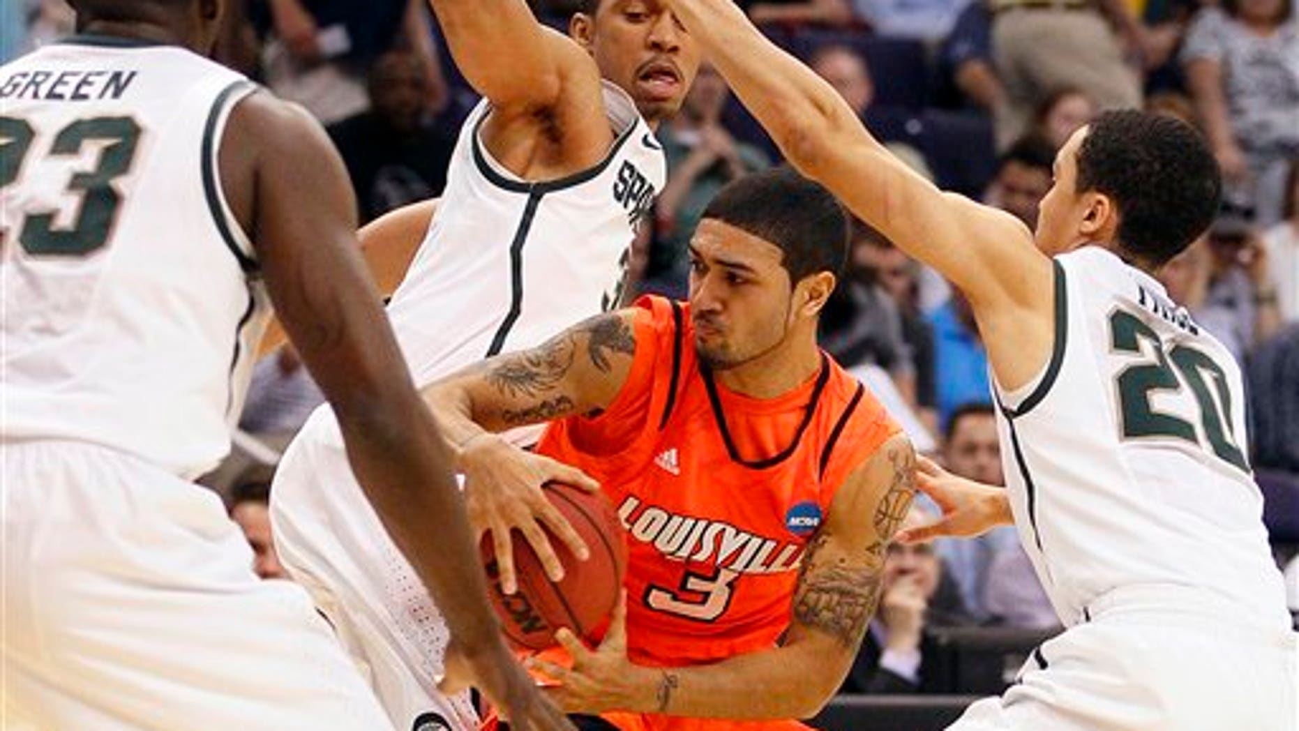 March 22, 2012: Louisville's Peyton Siva (3) is trapped by Michigan State defenders, from left, Draymond Green, Brandan Kearney and Travis Trice during the first half of an NCAA men's college basketball tournament West Regional semifinal on Thursday in Phoenix.
