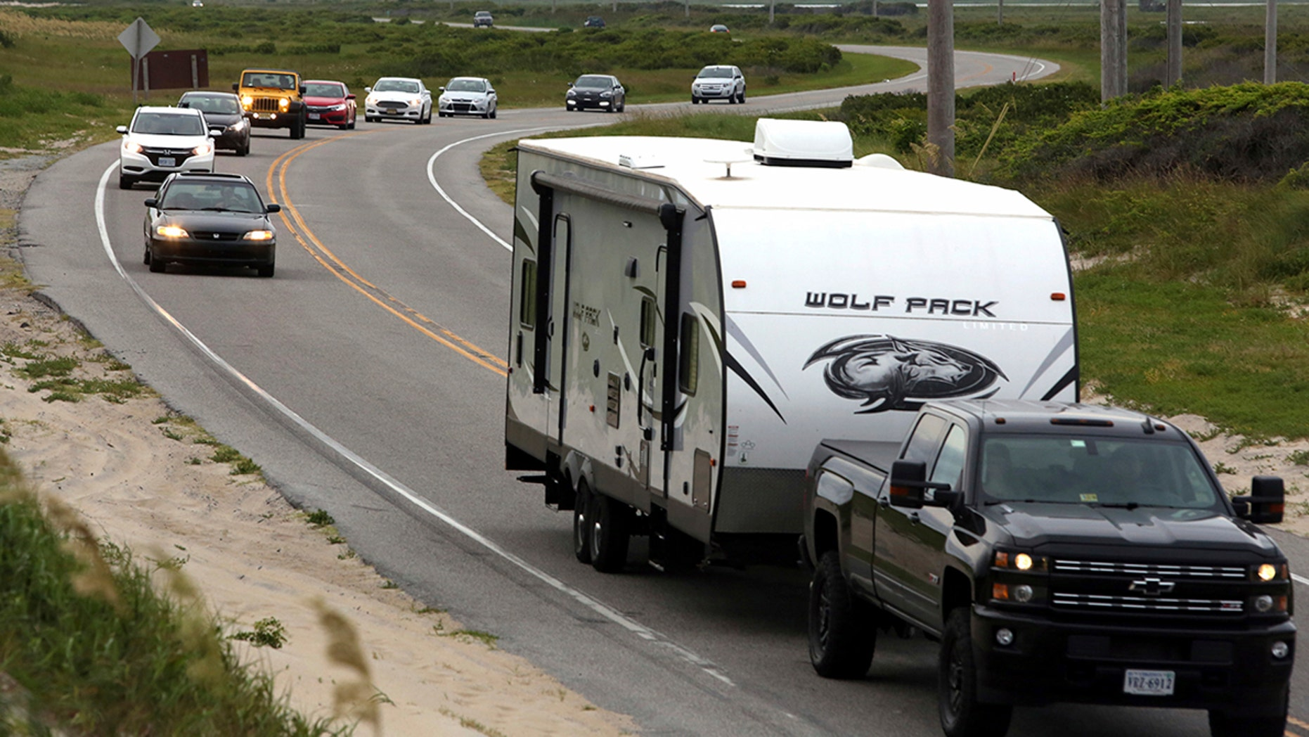 Vacationers head north on NC 12 on Hatteras Island, N.C., on Friday.