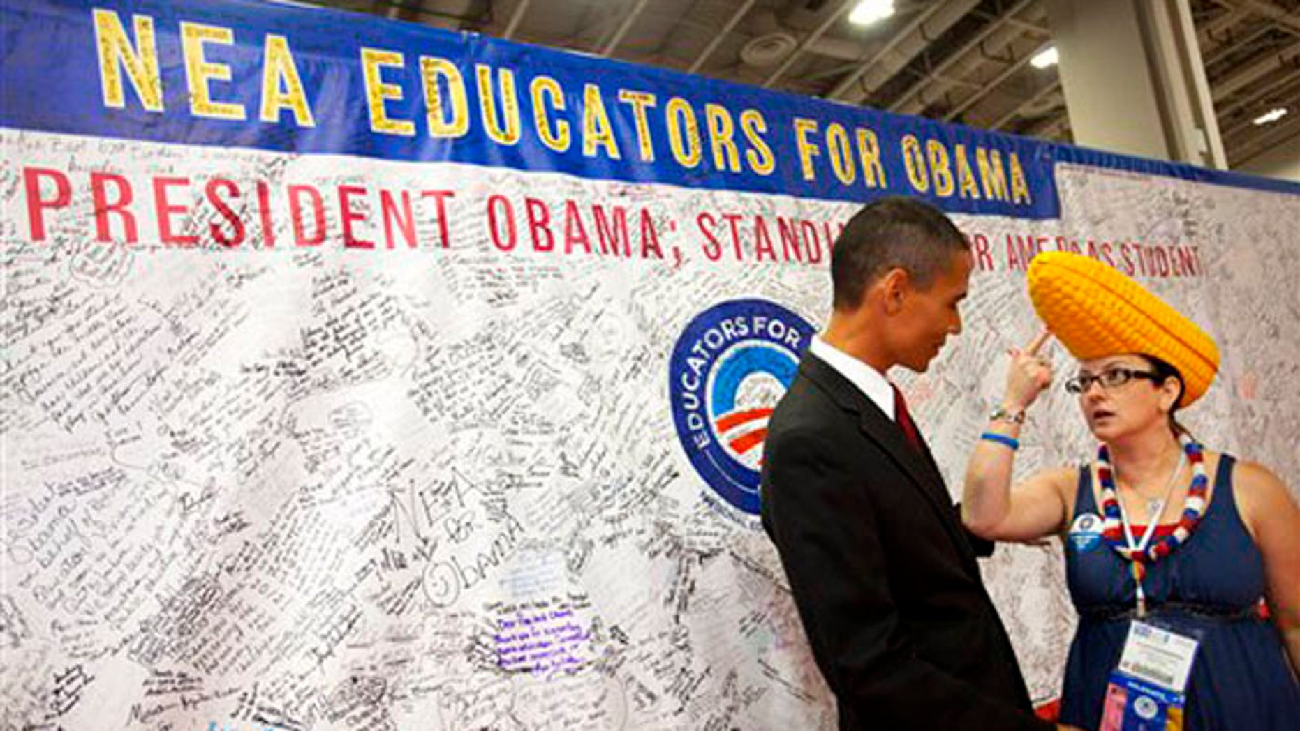 July 5, 2012: A teacher from Omaha, Nebraska, right, explains her corn hat to a President Obama impersonator and teacher in front of a banner of signatures in support of Obama at the National Education Association annual convention in Washington.