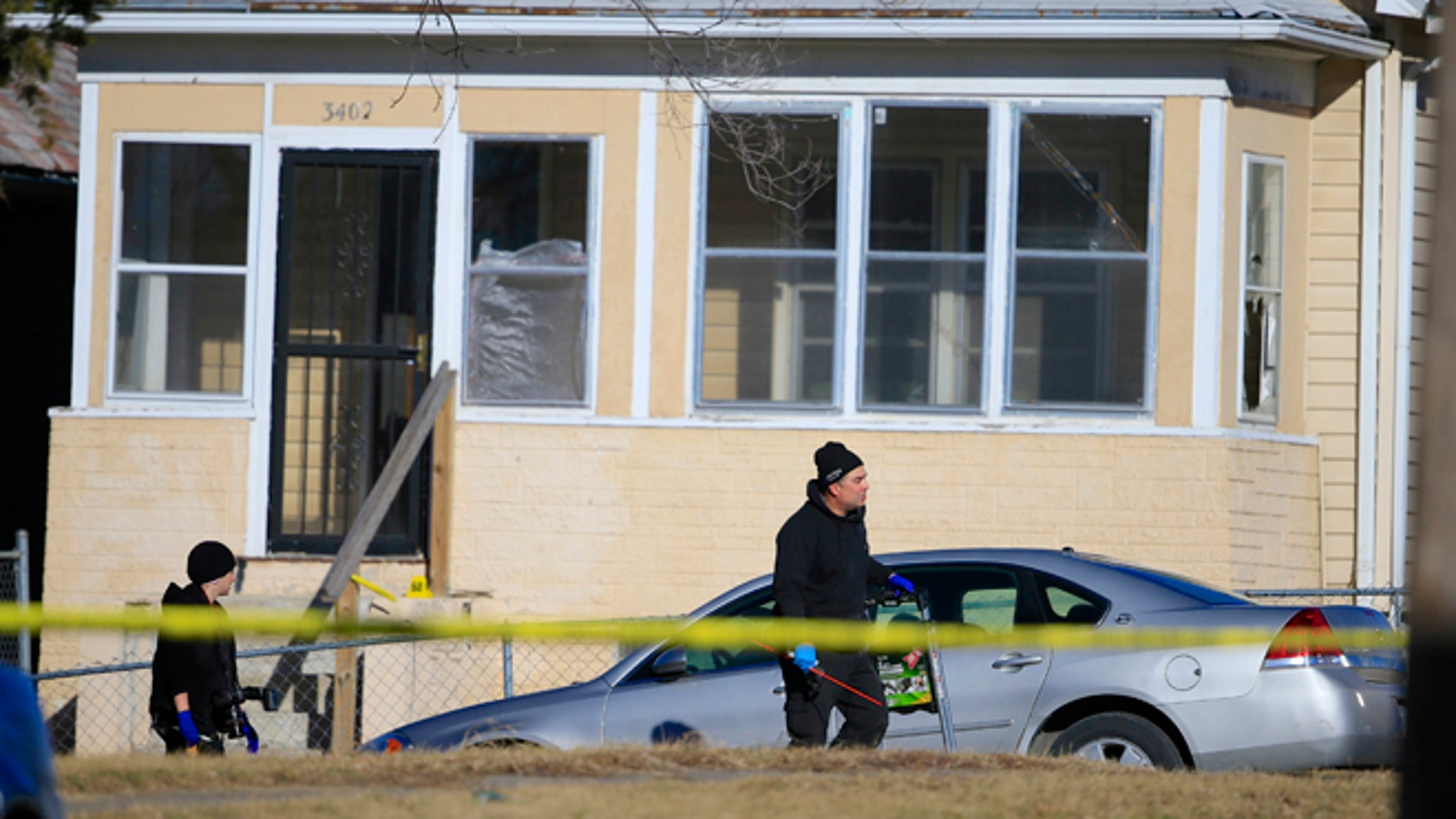 Jan. 24, 2015: A crime lab investigators walk past a house where a shooting in Omaha, Neb. (AP)