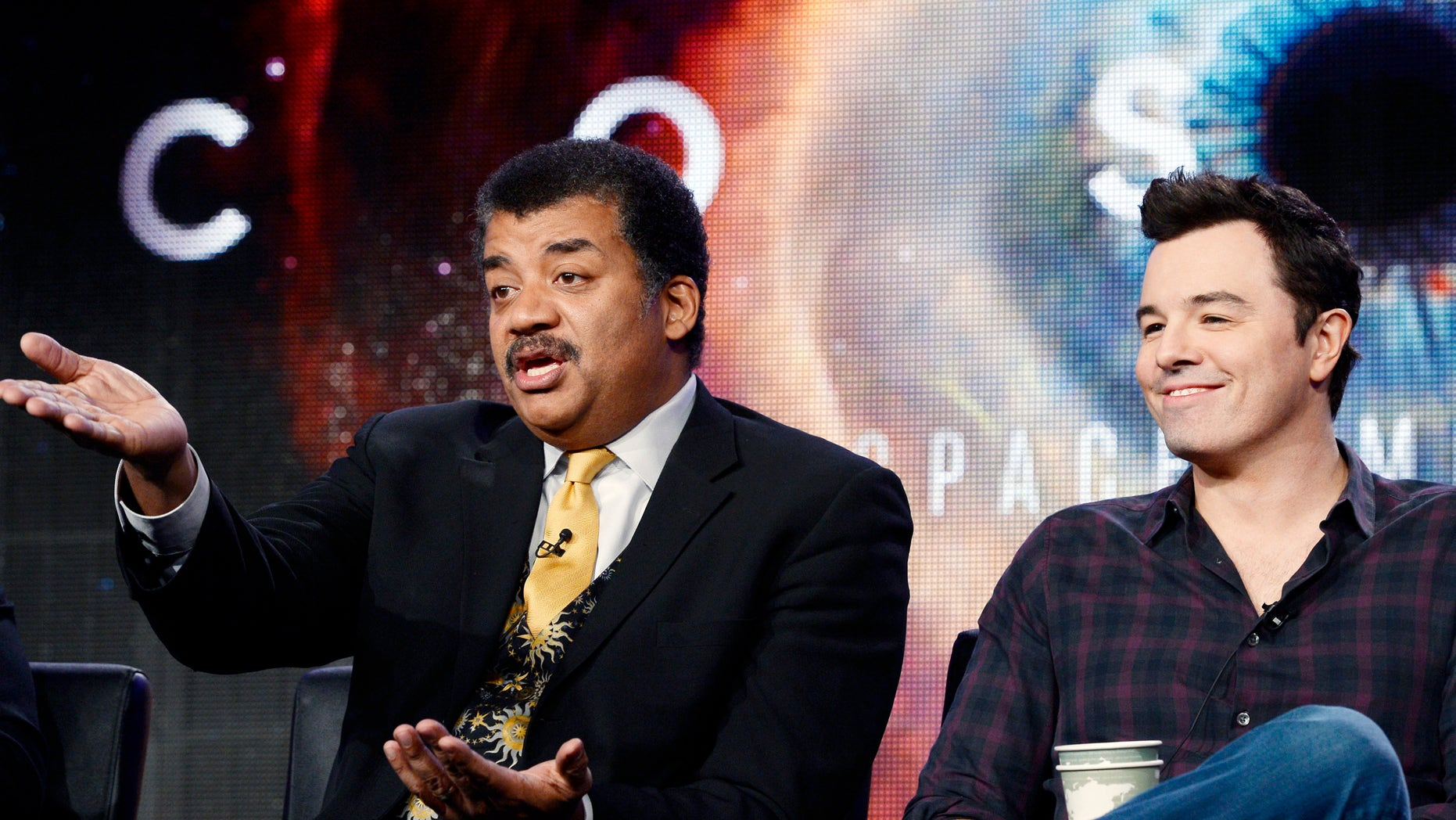 """January 13, 2014. Host Neil DeGrasse Tyson (L) and Seth MacFarlane, executive producer of  """"Cosmos,"""" participate in Fox Broadcasting Company's part of the Television Critics Association (TCA) Winter 2014 presentations in Pasadena, California."""