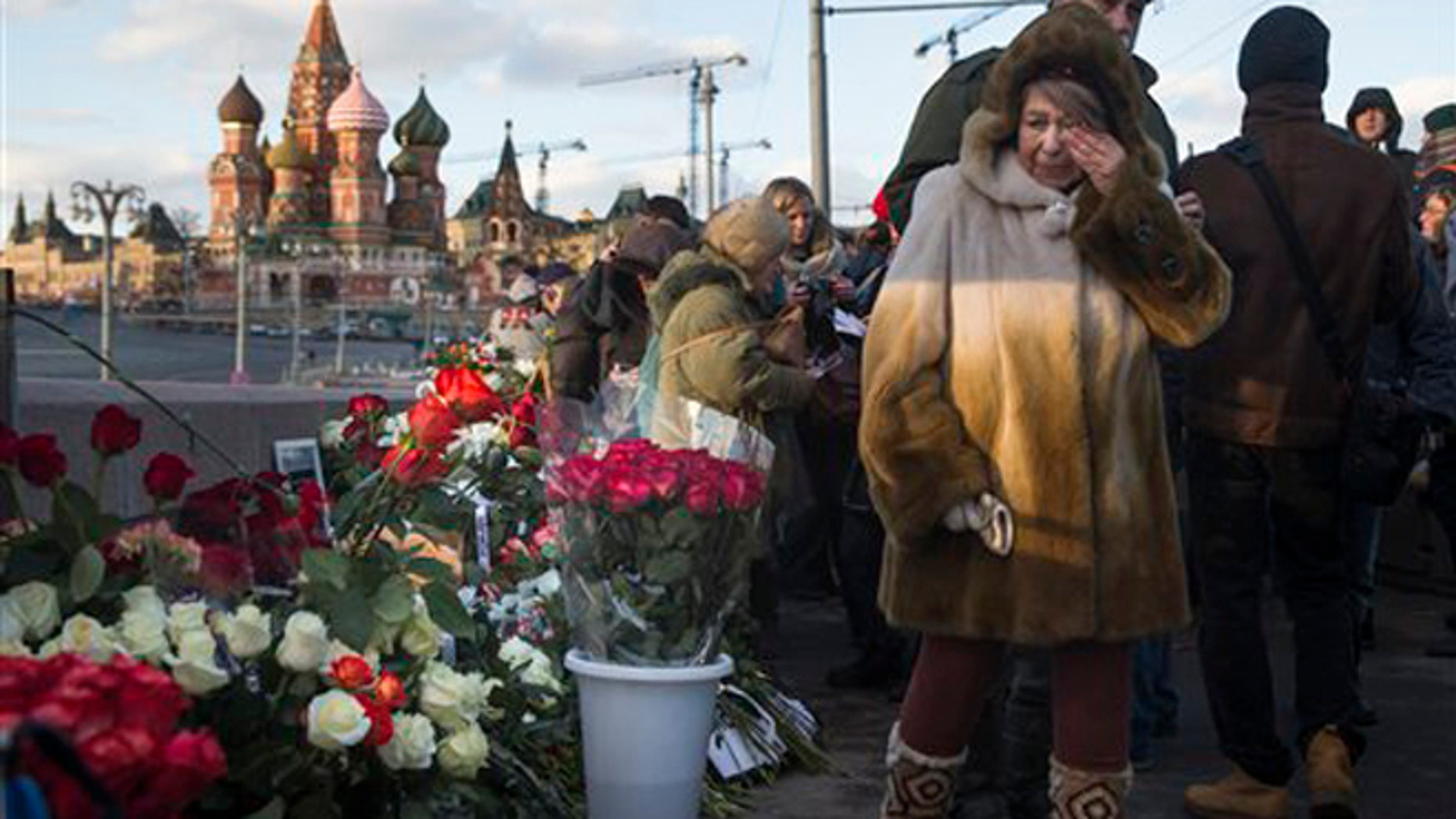 People lay flowers at the place where Russian opposition leader Boris Nemtsov was gunned down a year ago, marking the anniversary of his killing, in Moscow, with St. Basil Cathedral in the background, Russia, Saturday, Feb. 27, 2016. (AP Photo/Pavel Golovkin)