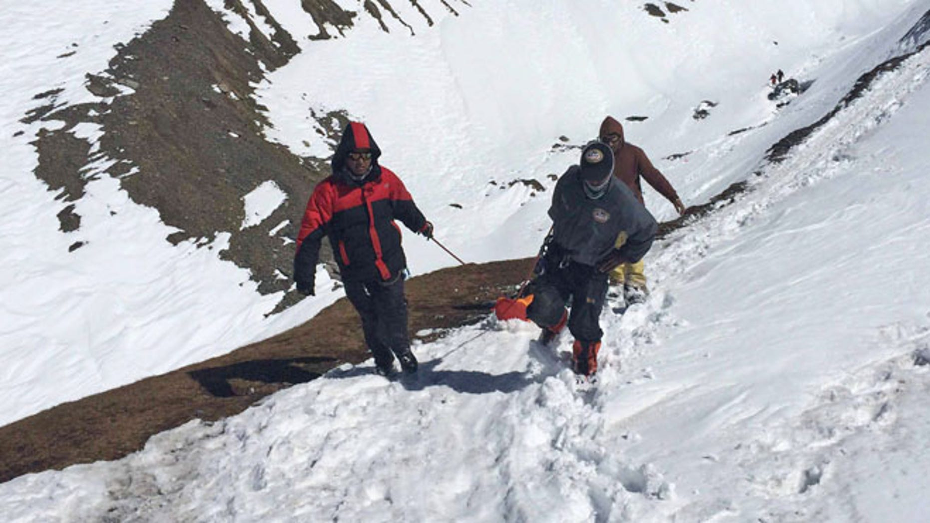 Oct. 17, 2014: In this handout photo provided by the Nepalese army, rescue team members carry the body of an avalanche victim at Thorong La pass area in Nepal