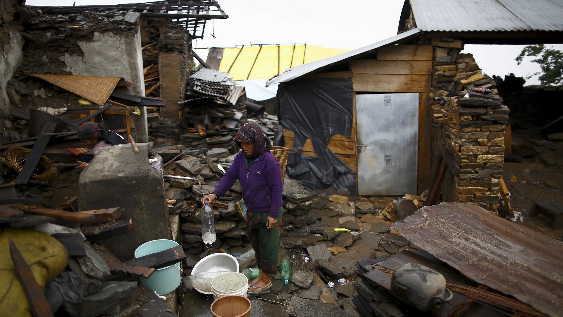 An earthquake victim fills water from a tap near the debris of a collapsed house at Barpak village at the epicenter of the April 25 earthquake in Gorkha district, Nepal, May 21, 2015. REUTERS/Navesh Chitrakar