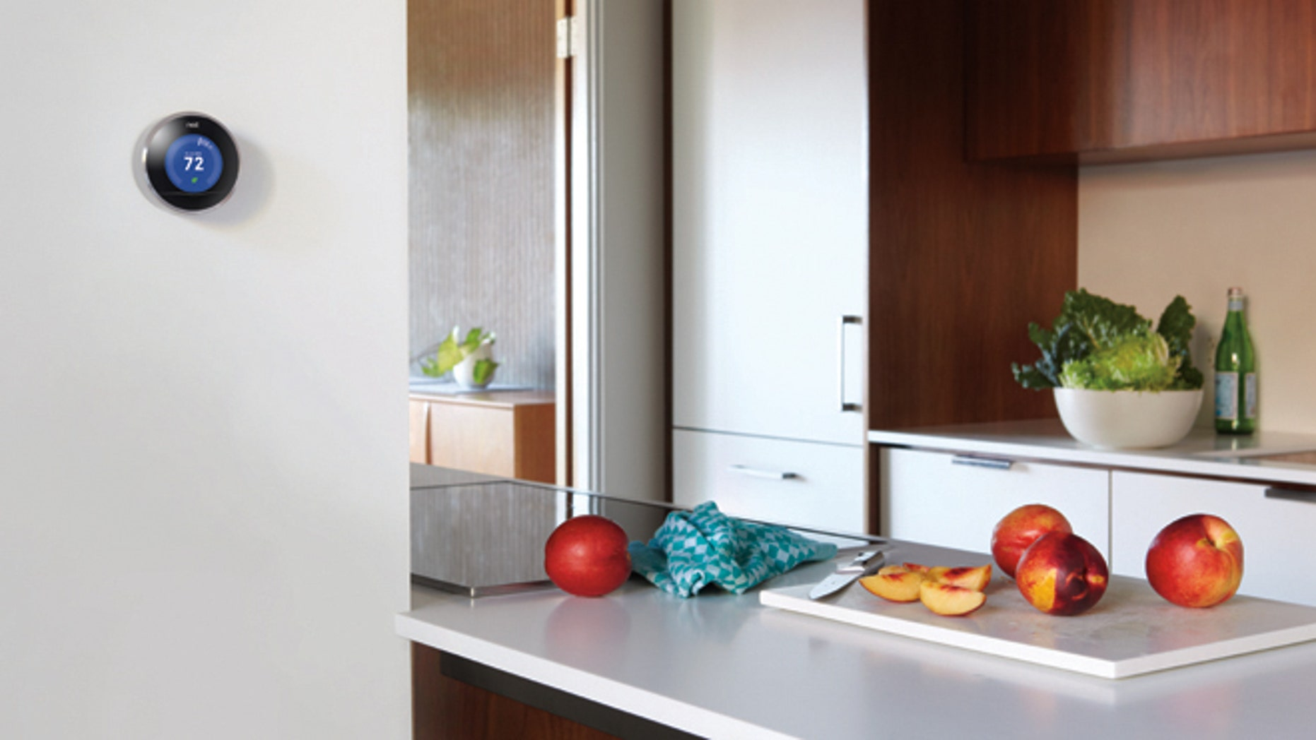 A Nest smart thermostat is seen on the wall of a kitchen.
