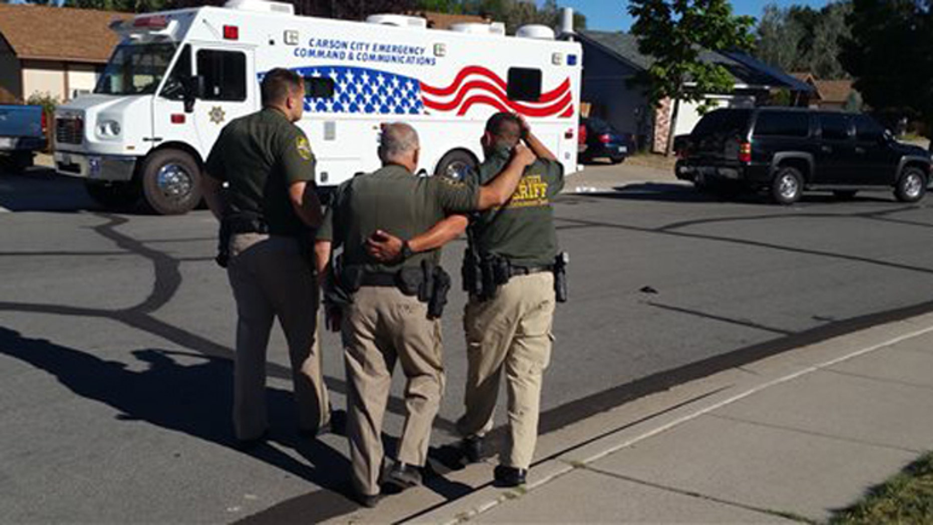 Aug. 15, 2015: Carson City Sheriff's Department deputies comfort each other outside the scene of a fatal shooting in Carson City, Nev., that left an officer and a suspect dead.