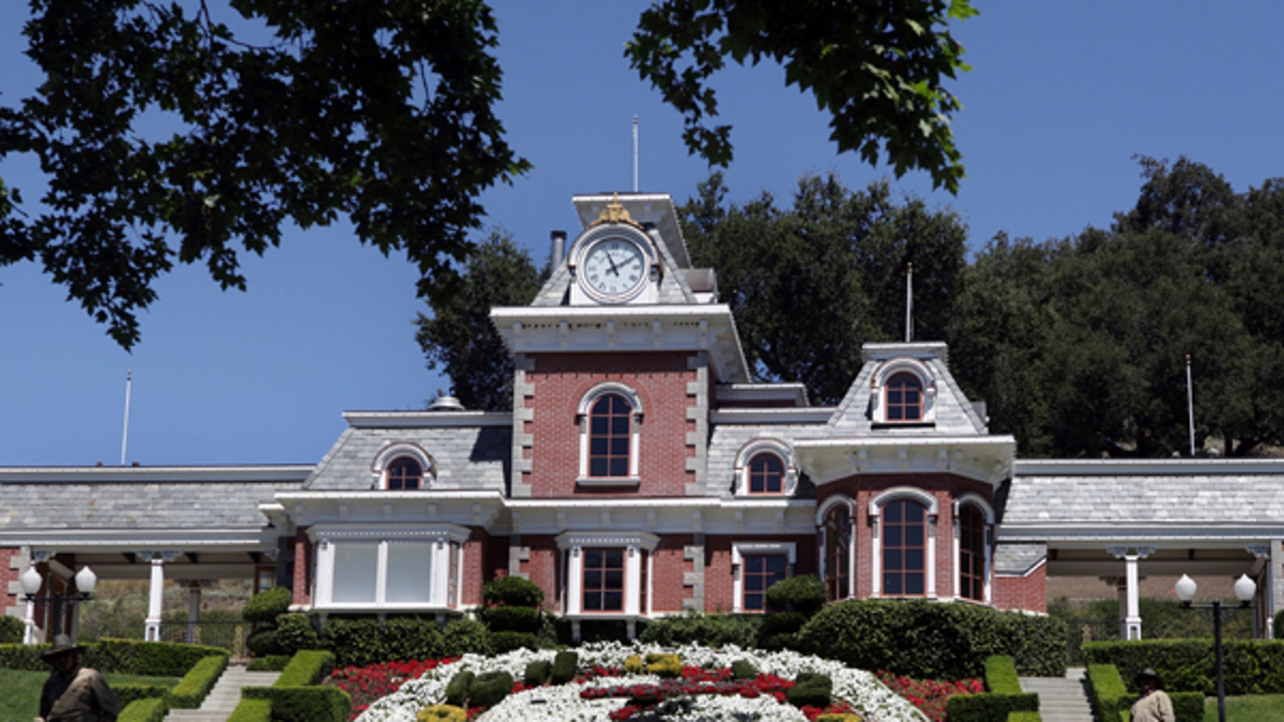 FILE - In this July 2, 2009, file photo, workers standby at the train station at Neverland Ranch in Los Olivos, Calif. Michael Jackson's former home has been renamed Sycamore Valley Ranch. The Los Angeles Times reported March 1, 2017, that it had been relisted for sale for $67 million. (AP Photo/Carolyn Kaster, File)