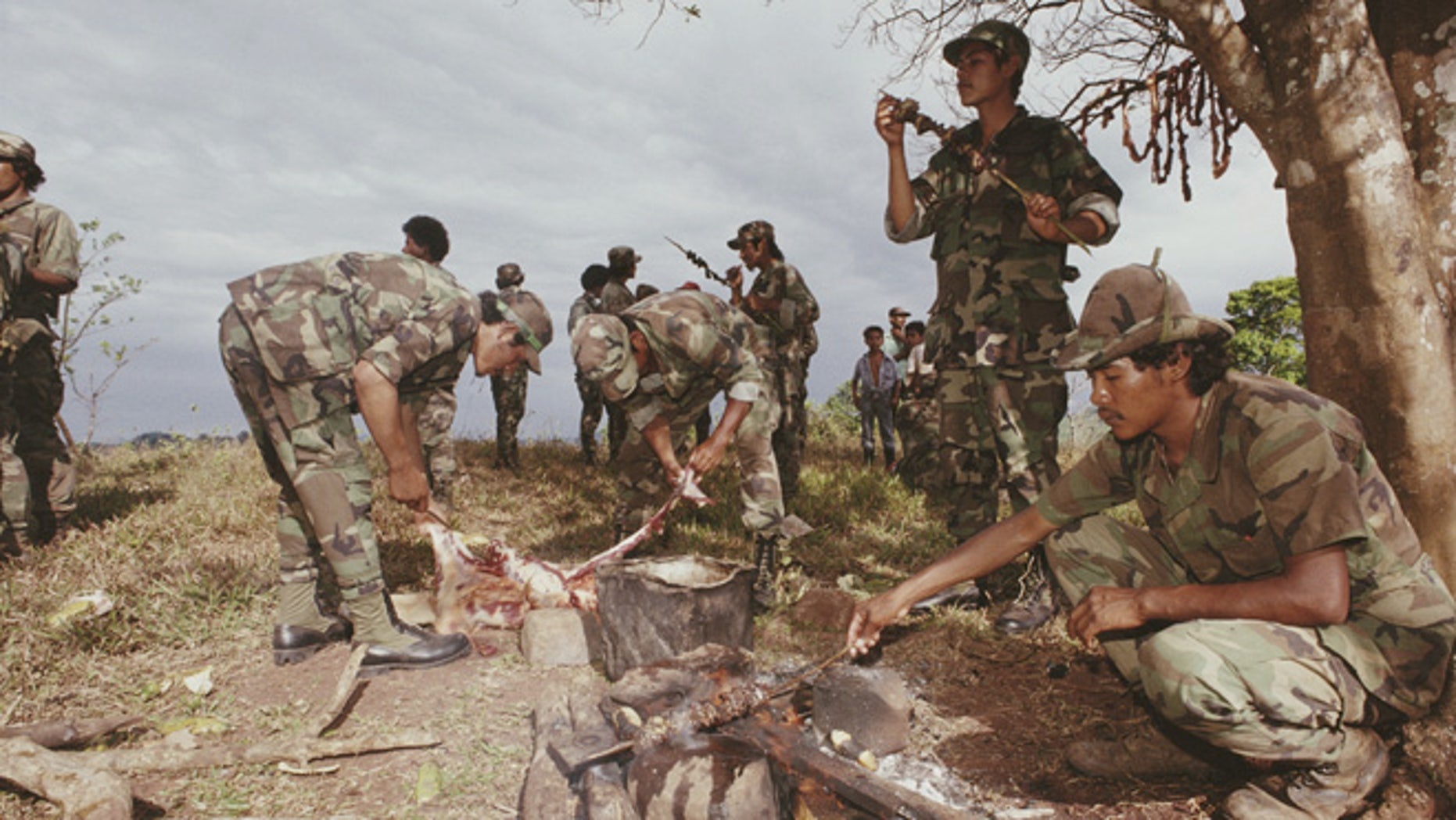 A group of contra guerillas cooking food in a disarmament zone, which they have just entered, Nicaragua, 1990. (Photo by Scott Wallace/Getty Images)