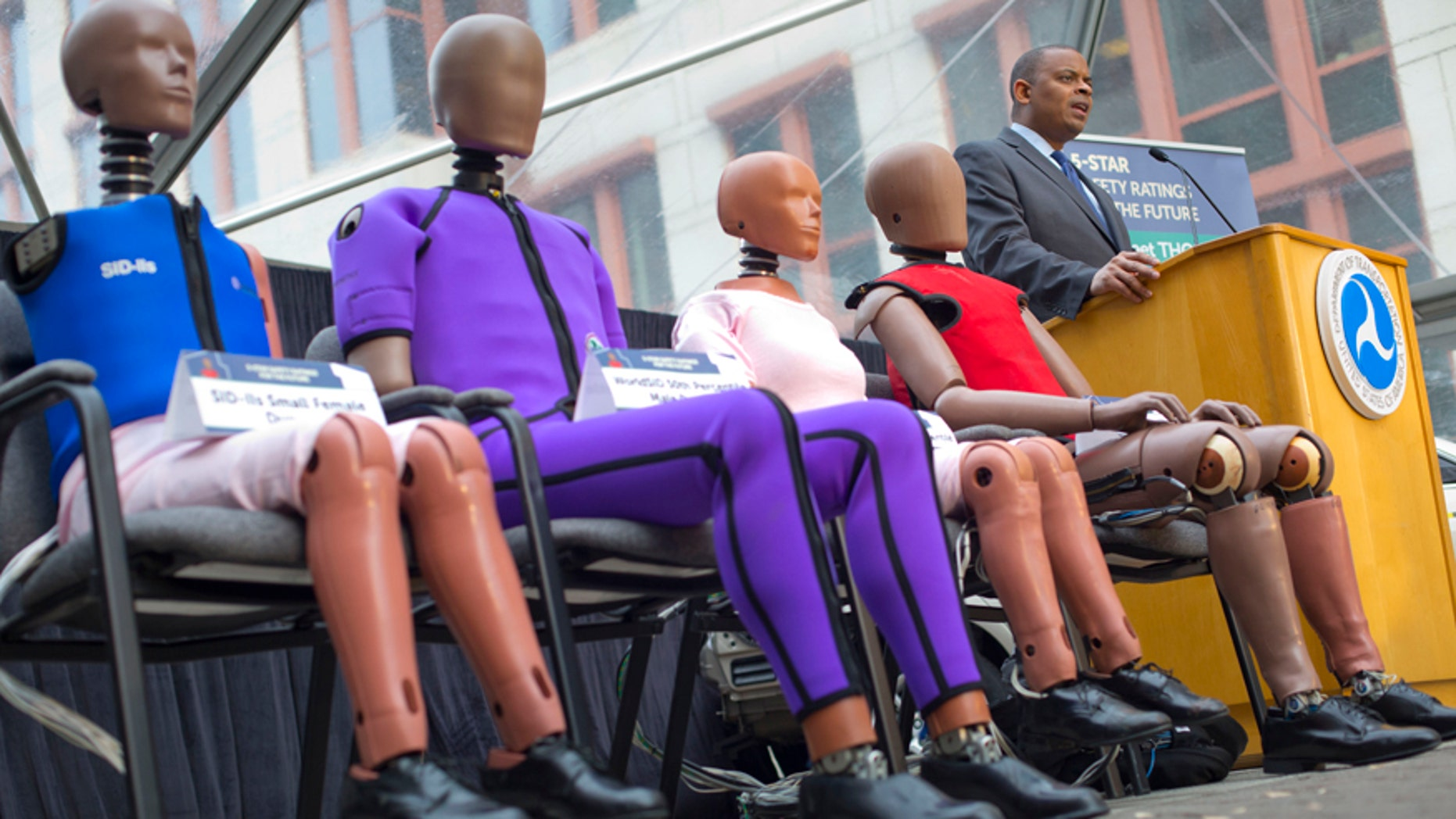 Transportation Secretary Anthony Foxx, with new crash test dummies called 'THOR', during the announcement for plans to update its safety rating system for new cars to include whether the car has technology to avoid crashes, in addition to how well it protects occupants in accidents in Washington, Tuesday, Dec. 8, 2015. In addition, the crash tests will be improved to include accidents in which cars collide at an angle, and they will use improved crash-test dummies that better represent how accidents impact the human body. And the rating system will reward cars designed to protect pedestrians who are struck by them.(AP Photo/Pablo Martinez Monsivais)